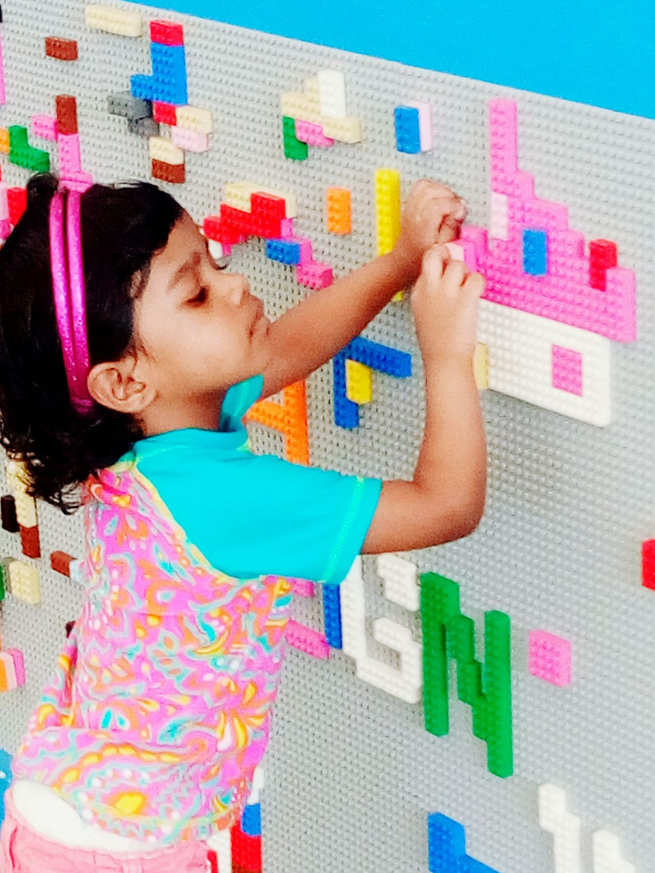 Little girl continues building lego bricks, making a pink house Child Multi Colored Childhood Black Hair One Person Day Little girl Build lego Bricks Pink House