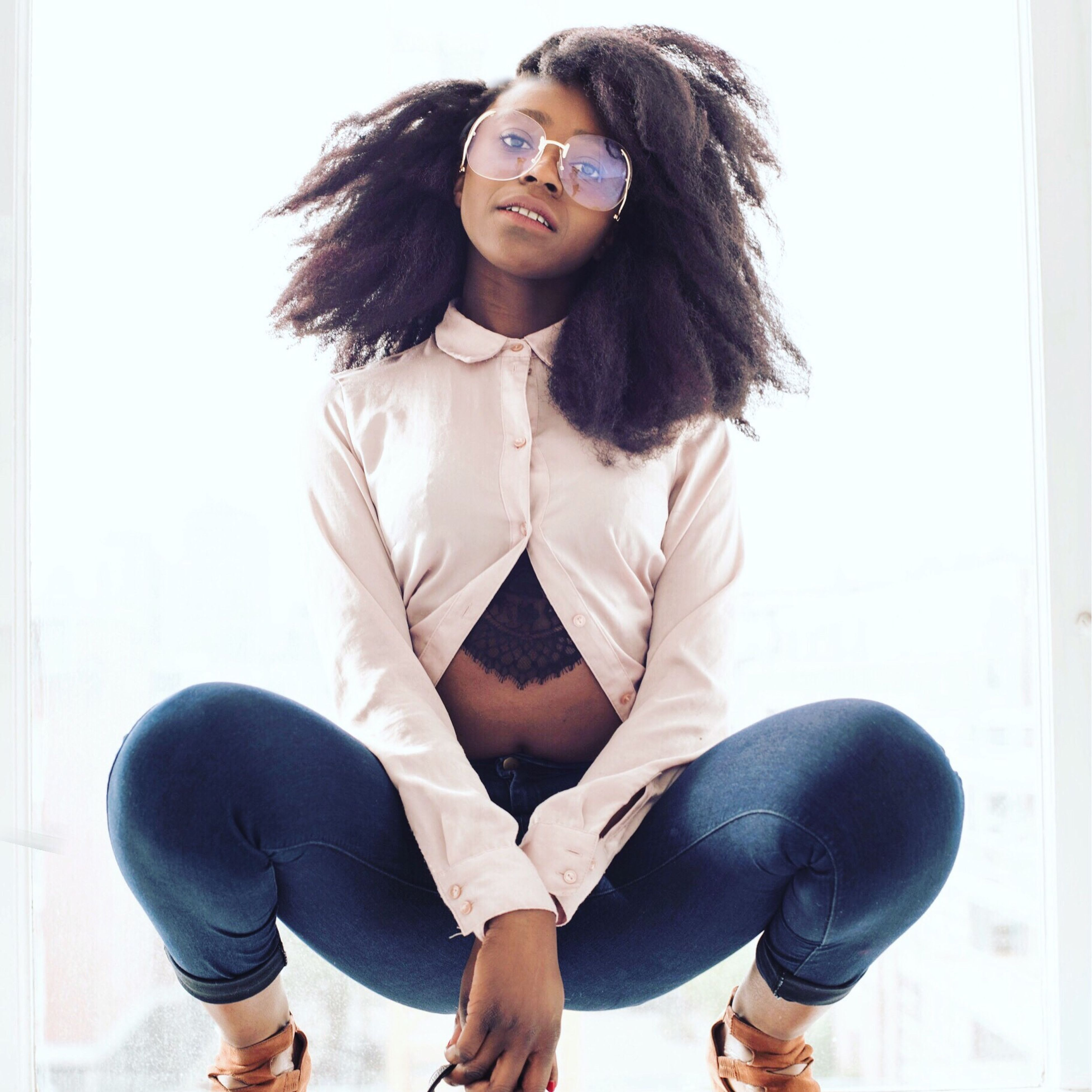 young adult, looking at camera, portrait, black hair, one person, casual clothing, indoors, young women, white background, beautiful woman, eyeglasses, sitting, studio shot, real people, confidence, full length, lifestyles, curly hair, happiness, one young woman only, day, adult, people, adults only