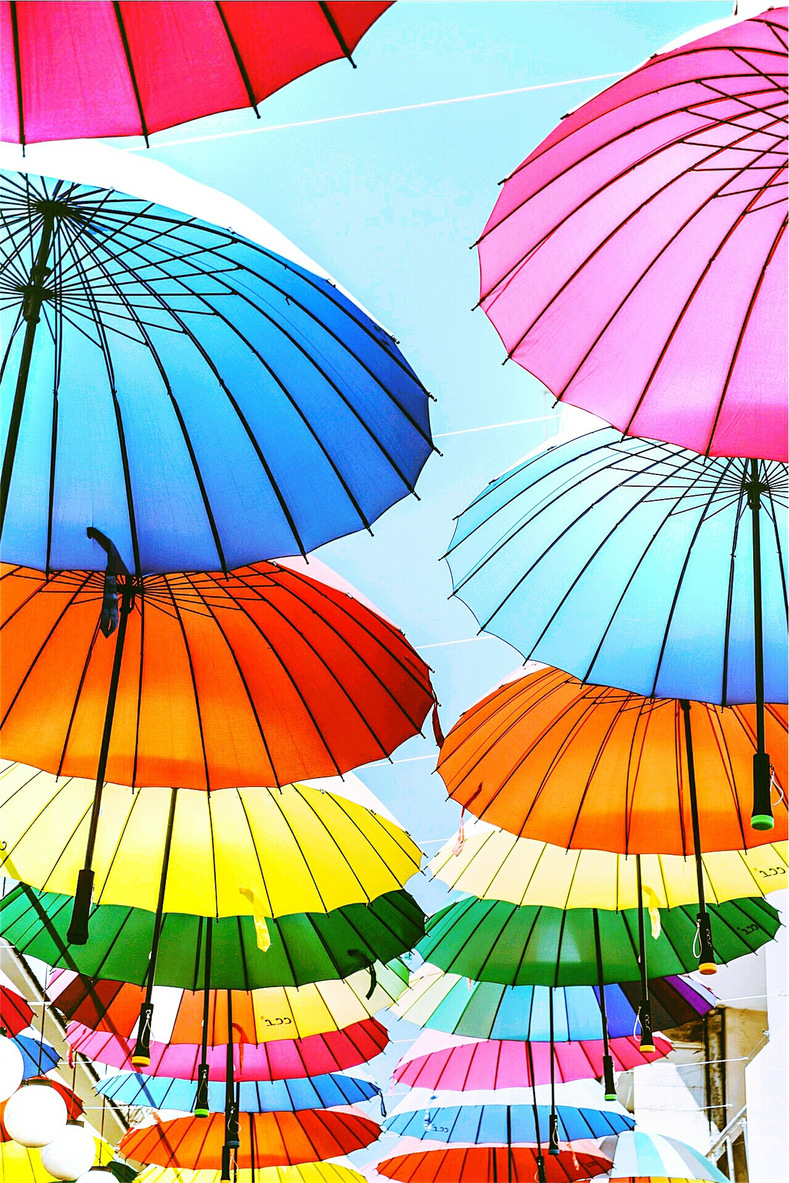 umbrella, multi colored, low angle view, parasol, clear sky, beach umbrella, sky, sunshade, colorful, flag, hanging, protection, day, amusement park, decoration, pattern, blue, celebration, hot air balloon, outdoors