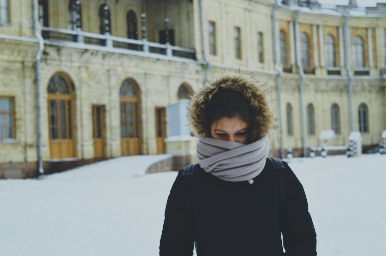 winter, real people, cold temperature, architecture, snow, one person, built structure, building exterior, lifestyles, outdoors, standing, day, warm clothing, young adult, people
