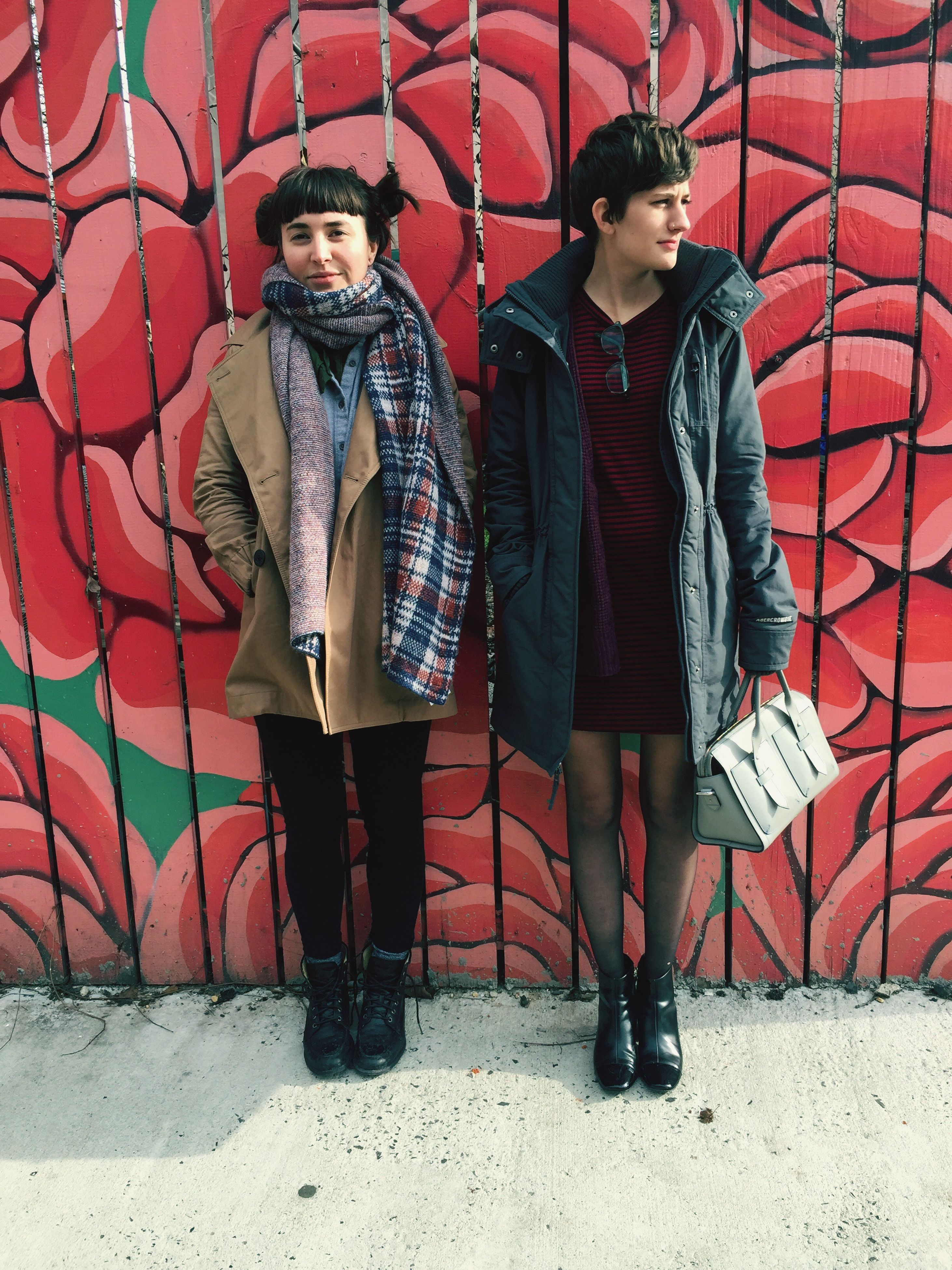 young adult, lifestyles, front view, casual clothing, looking at camera, portrait, standing, young women, leisure activity, person, graffiti, red, full length, wall - building feature, smiling, built structure, jacket, traditional clothing