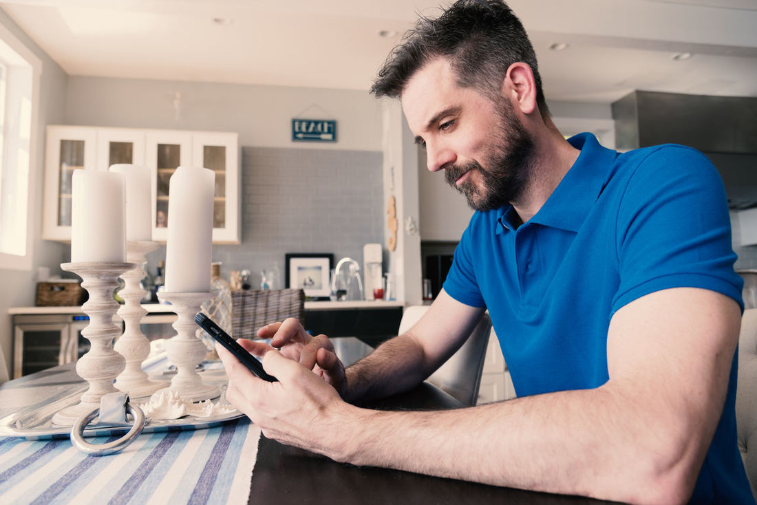 Caucasian male sitting at table using mobile phone wearing a blue polo shirt showing muscular arm. Adult Dating Mobile Phone Social Apps Arm Beard Blue Caucasian Fitness Handsome Healthy Eating Interface Male Media Messaging Model Polo Shirt  Professional Technology Telecommunication Telecommute Texting Using Wireless Technology