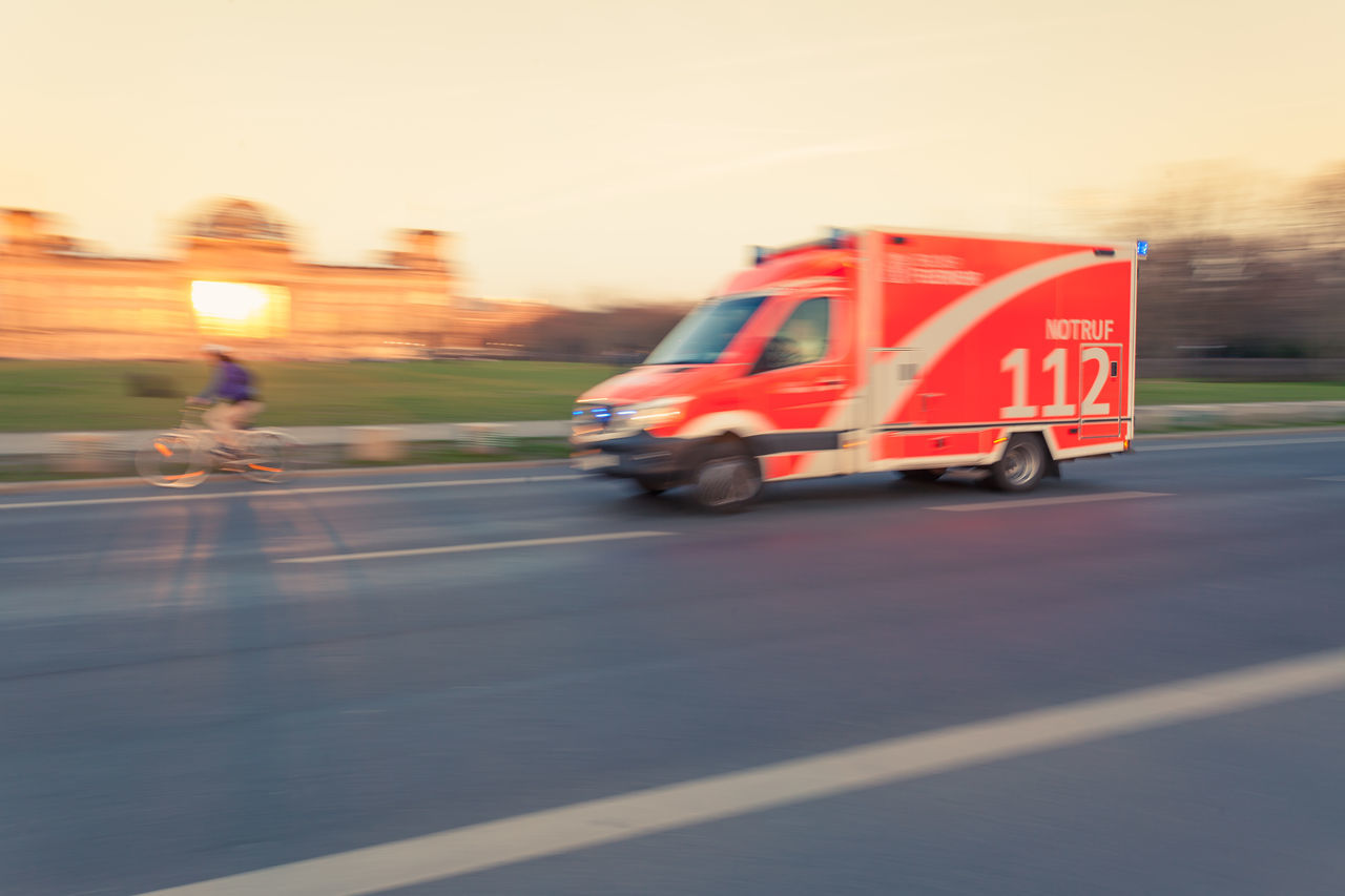 Ambulance, emergency with high speed on city street in Berlin, motion blur zoom effect at sunset Ambulance Berlin Blurred Motion Car Day Downtown Driving Emergency Fire Department Germany Motion Motion Blur No People Outdoors Reichstag Road Sky Speed Street Sunset Transportation