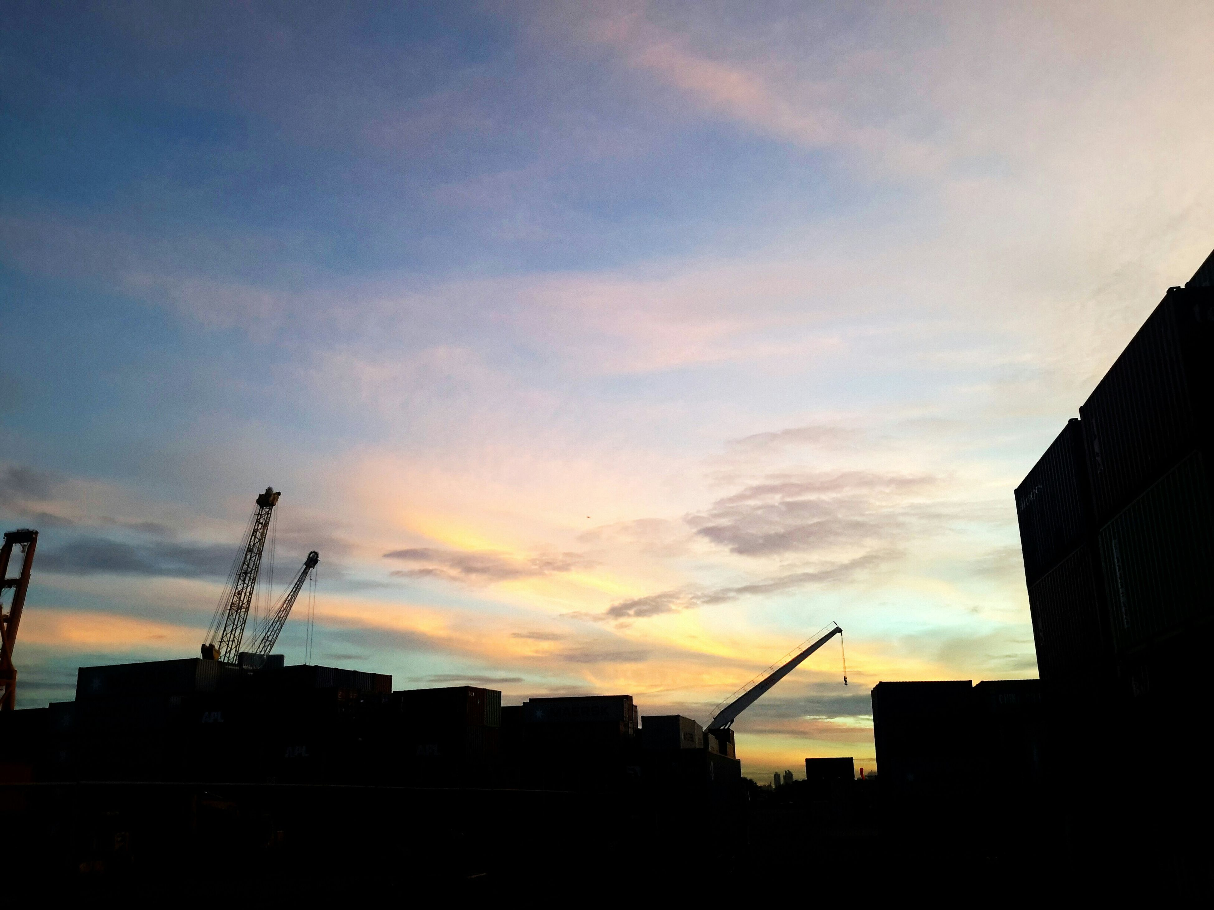 silhouette, building exterior, architecture, built structure, sunset, sky, low angle view, city, cloud - sky, construction site, building, cloud, crane - construction machinery, orange color, outdoors, crane, residential structure, development, residential building, dusk