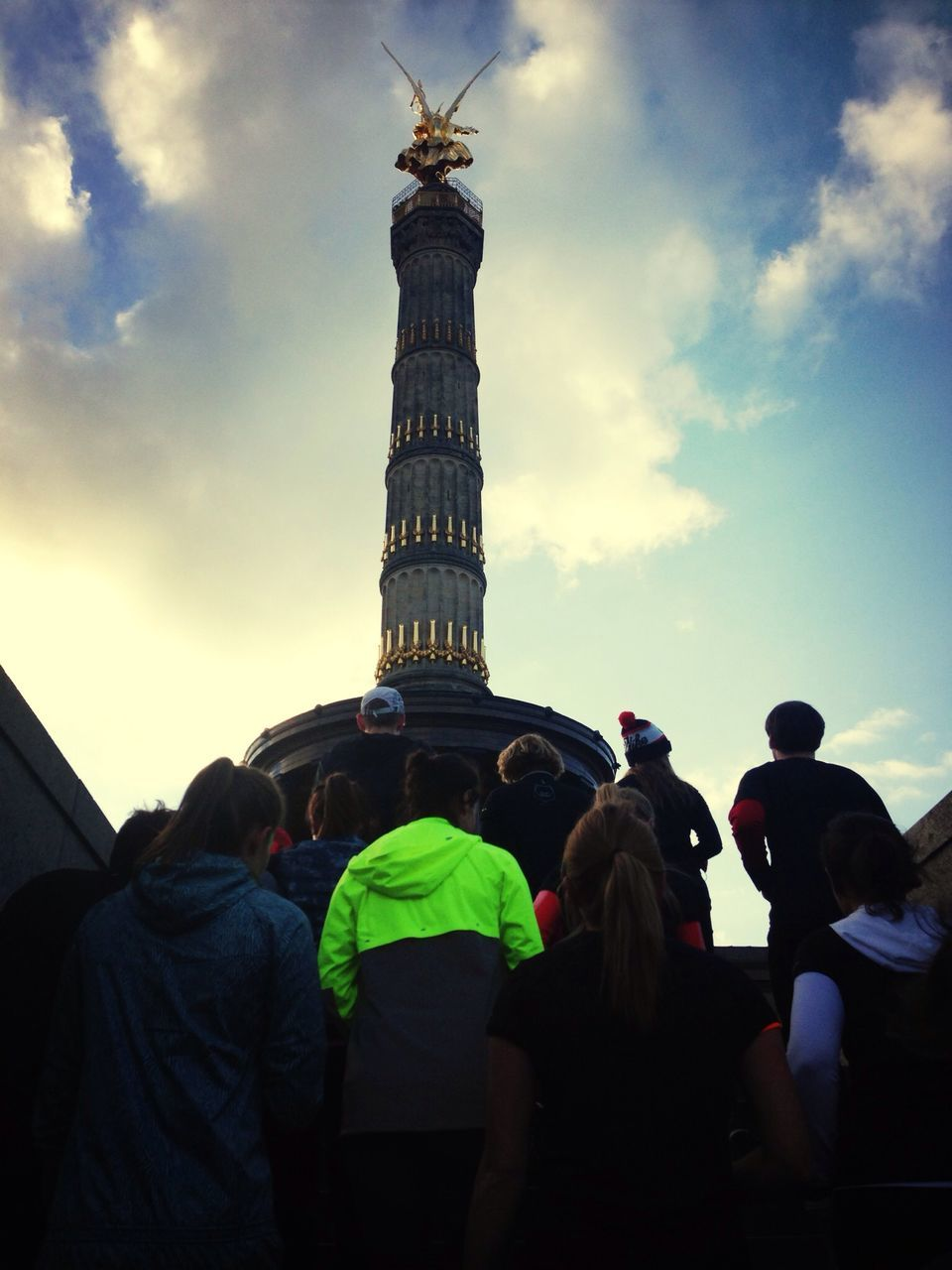 travel destinations, statue, large group of people, cloud - sky, sky, tourism, travel, sculpture, low angle view, architecture, real people, history, women, men, built structure, architectural column, outdoors, lifestyles, day, city, crowd, adult, people