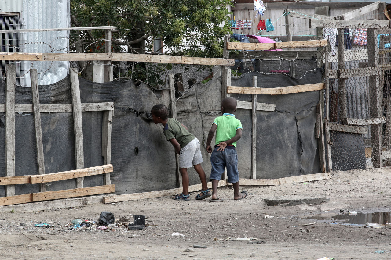 Two boys looking through the hole in a fence of their neighbourhood Blikkiesdorp Building Exterior Built Structure Children Day Full Length Lifestyles Outdoors Peephole People Rascal Real People Rear View Township Life Tree Two People