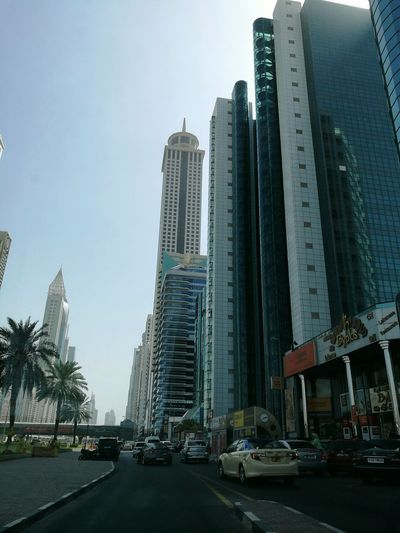 Hello World Taking Photos City Life Cityscapes Buildings Building Exterior Architecture Architectural Detail High Rise Building Building And Sky Sky Road Palm Trees Cars