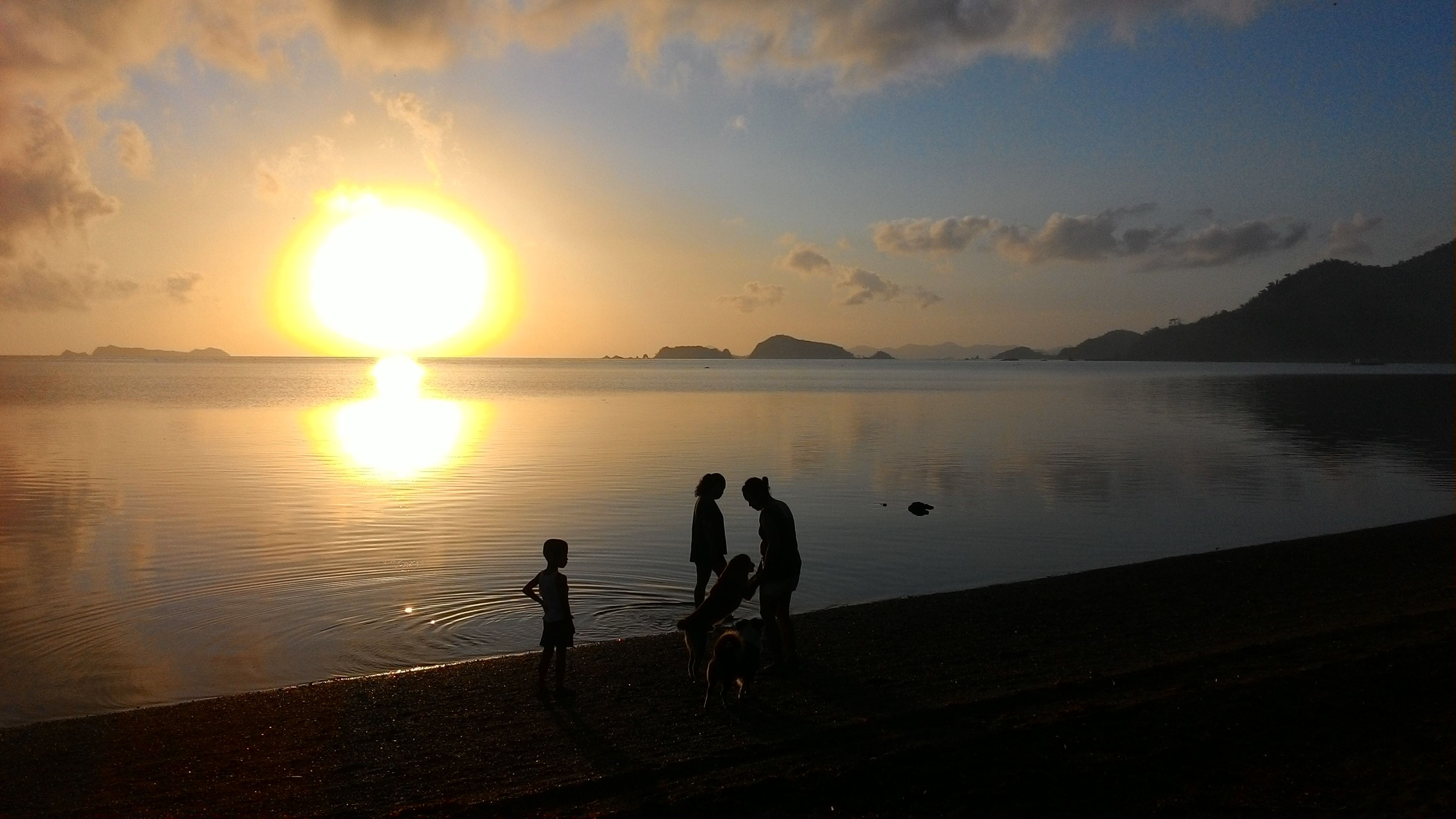 sunset, water, silhouette, nature, beauty in nature, scenics, sky, sun, sea, reflection, real people, tranquility, tranquil scene, lifestyles, togetherness, vacations, men, sunlight, leisure activity, beach, cloud - sky, outdoors, standing, horizon over water, boys, two people, childhood, people