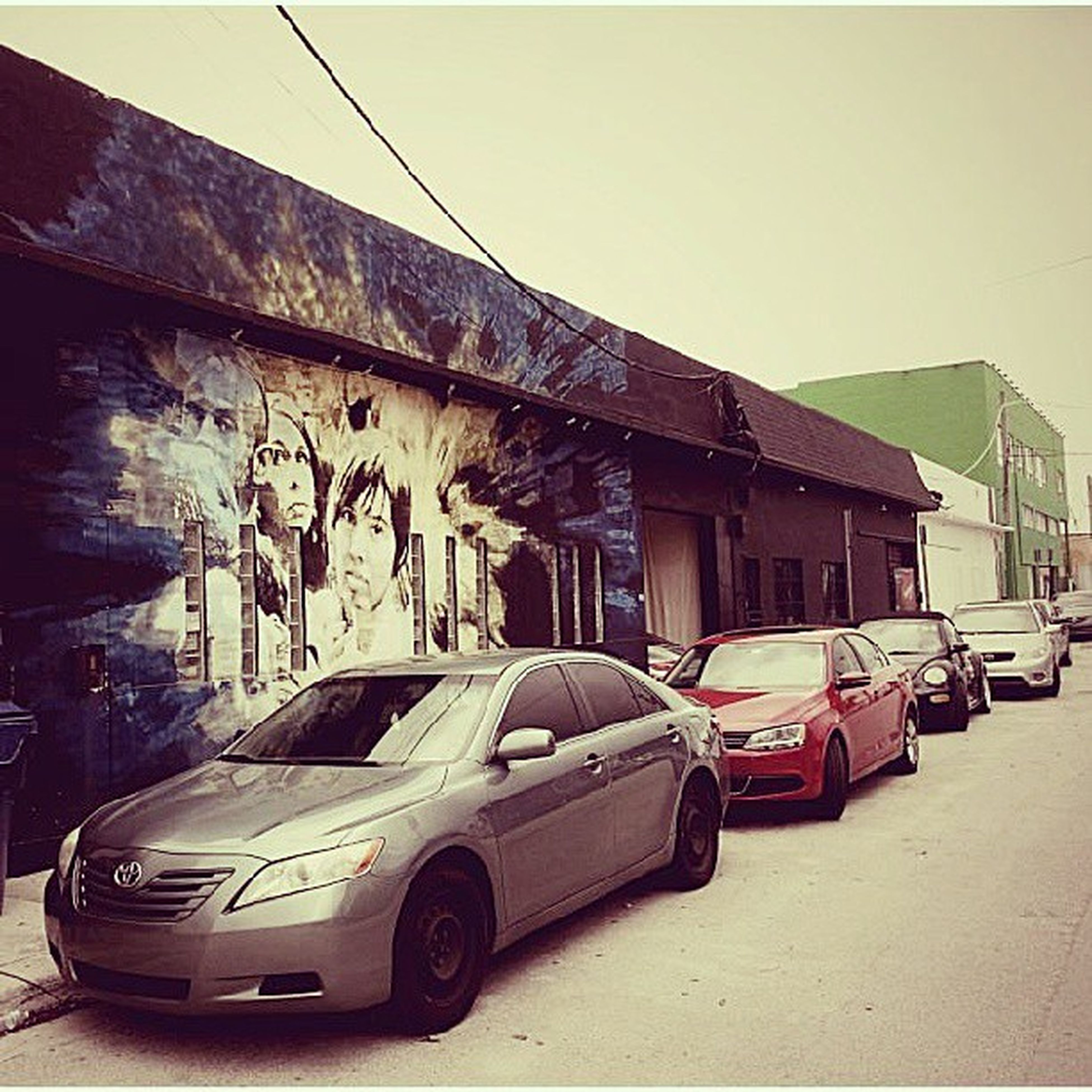 transportation, architecture, built structure, land vehicle, building exterior, car, mode of transport, graffiti, street, clear sky, road, parking, stationary, city, outdoors, day, no people, building, parked, wall - building feature