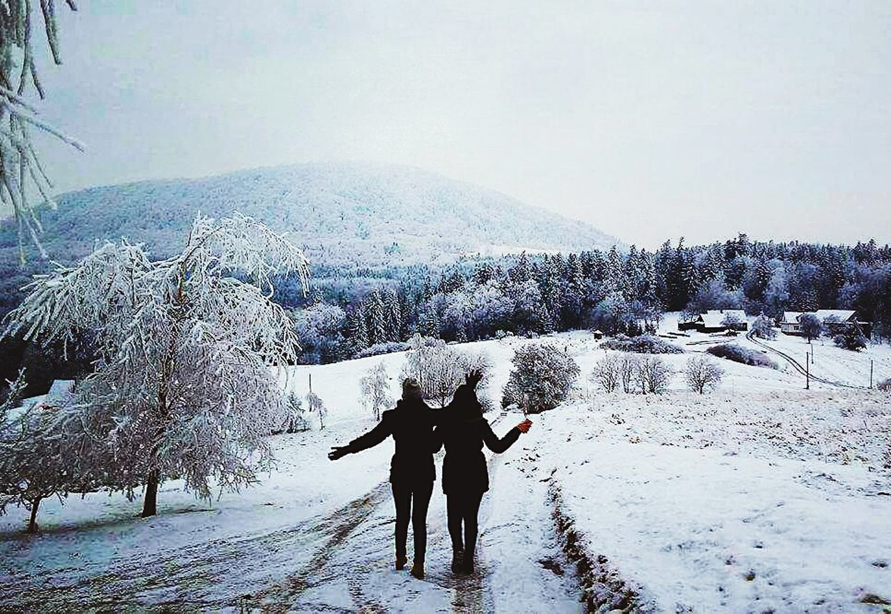 winter, snow, cold temperature, two people, nature, beauty in nature, domestic animals, scenics, frozen, togetherness, dog, pets, day, full length, real people, outdoors, men, tree, mammal, mountain, sky, warm clothing, people