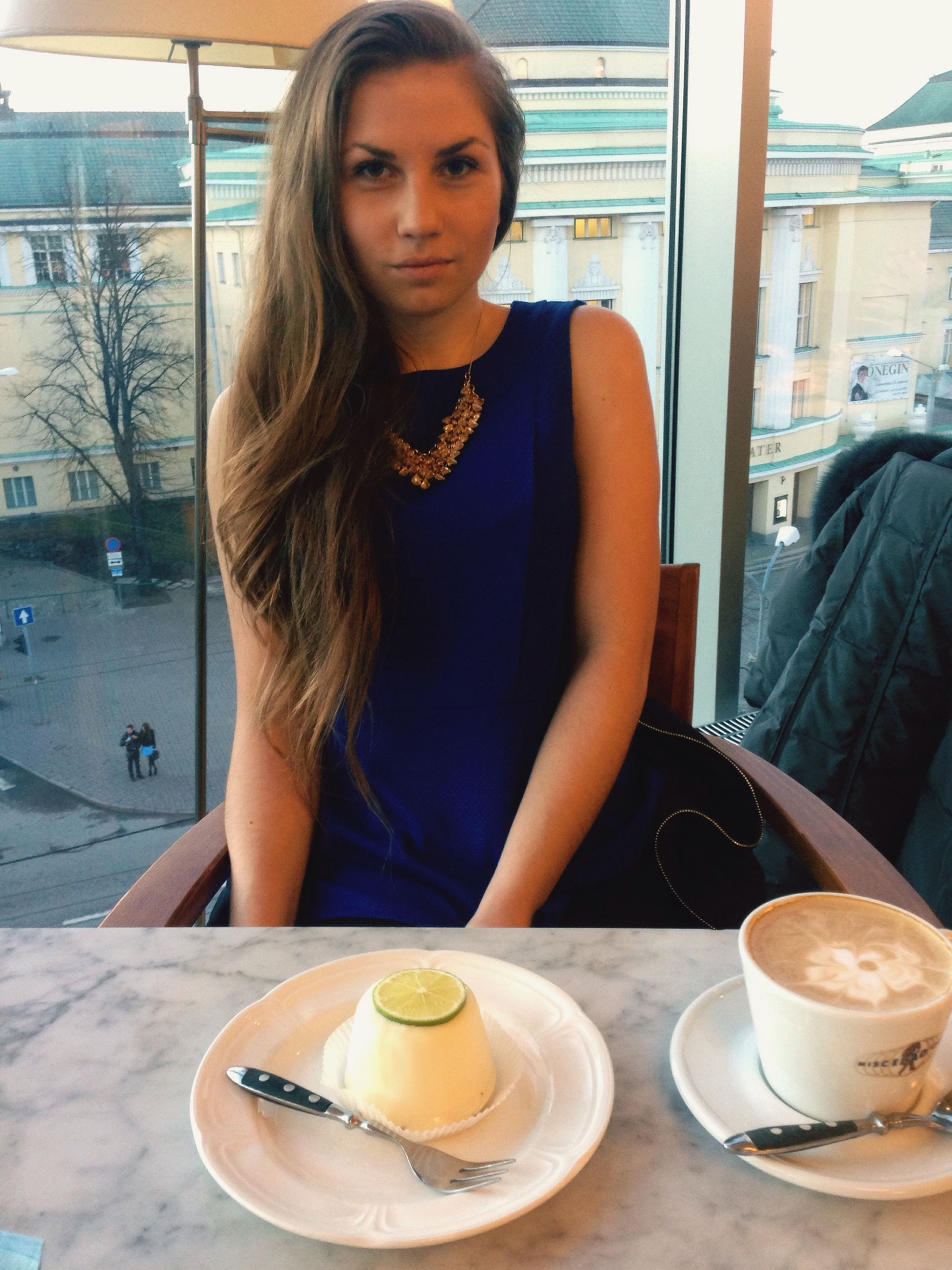 food and drink, drink, indoors, lifestyles, young adult, table, person, sitting, leisure activity, refreshment, young women, casual clothing, coffee cup, front view, restaurant, looking at camera, portrait, coffee
