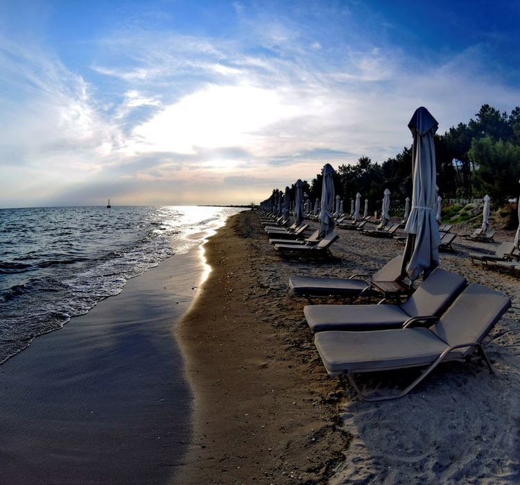 Deck chairs in a summer beach in a greek town Sea Beach Water Sand Sky Outdoors No People Nature Day Horizon Over Water Waterfront Tranquility Greece Beauty In Nature Built Structure Nature Architecture Deck Chairs Summertime Summer Sunset Cityscape Illuminated Summer Beach Halkidiki,Greece
