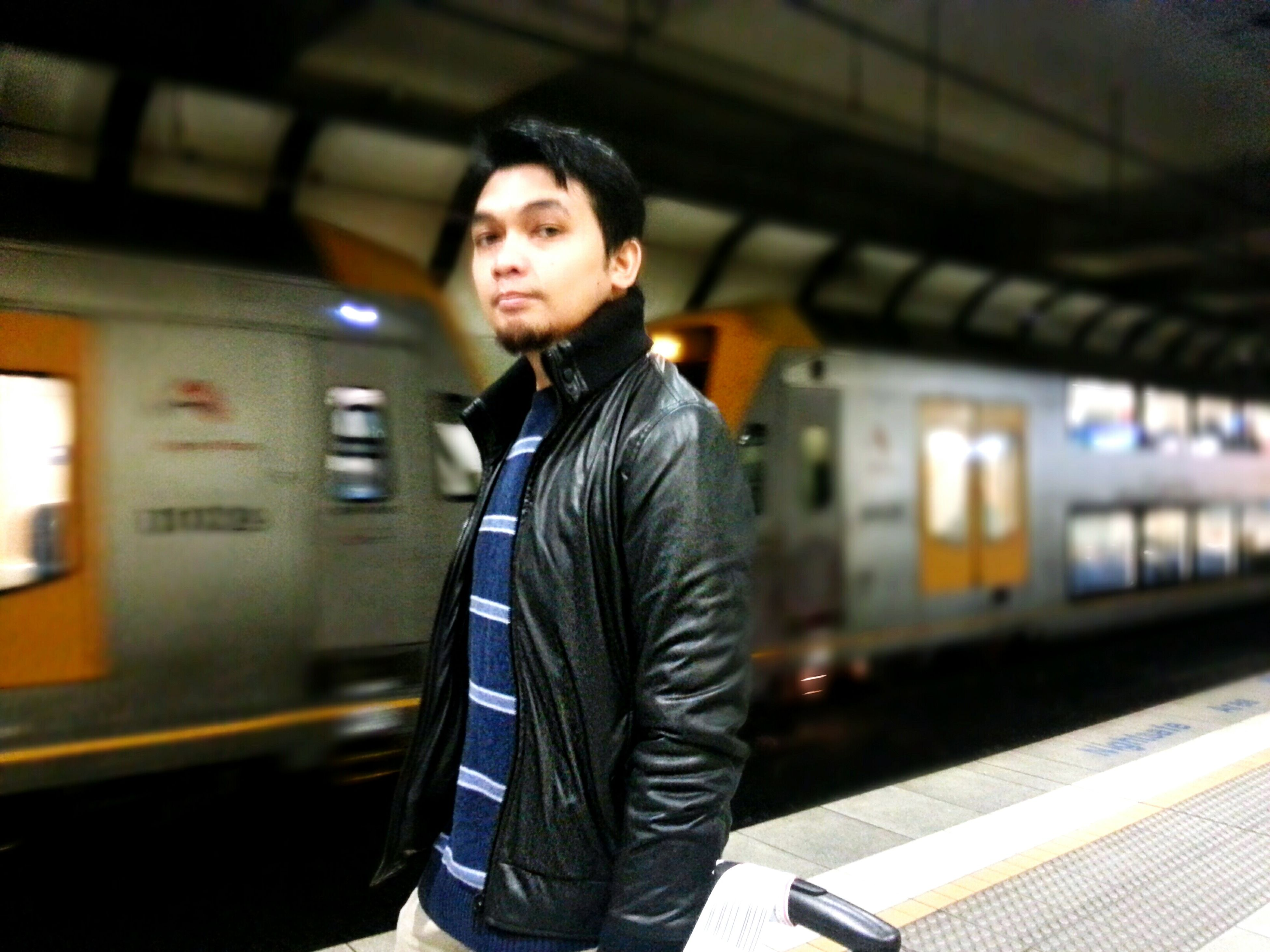 casual clothing, young adult, standing, lifestyles, three quarter length, person, front view, looking at camera, portrait, full length, leisure activity, young men, jacket, waist up, built structure, focus on foreground, transportation