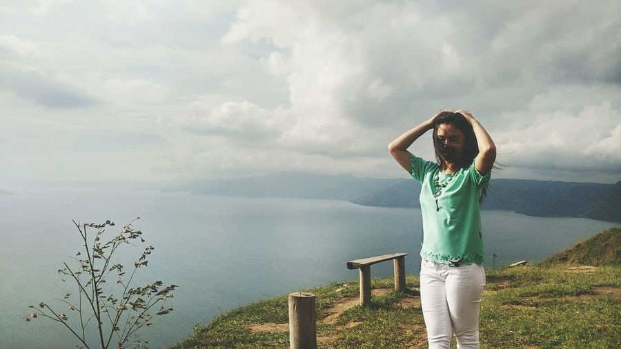 Feels free Lost In The Landscape EyeEm Selects One Person Cloud - Sky Standing Arms Raised Lake Human Body Part Outdoors People Only Women Day Sky Leisure Activity Casual Clothing Nature Adults Only Adult Discovery Vacations Nature Beauty In Nature Smartphonephotography INDONESIA LakeToba