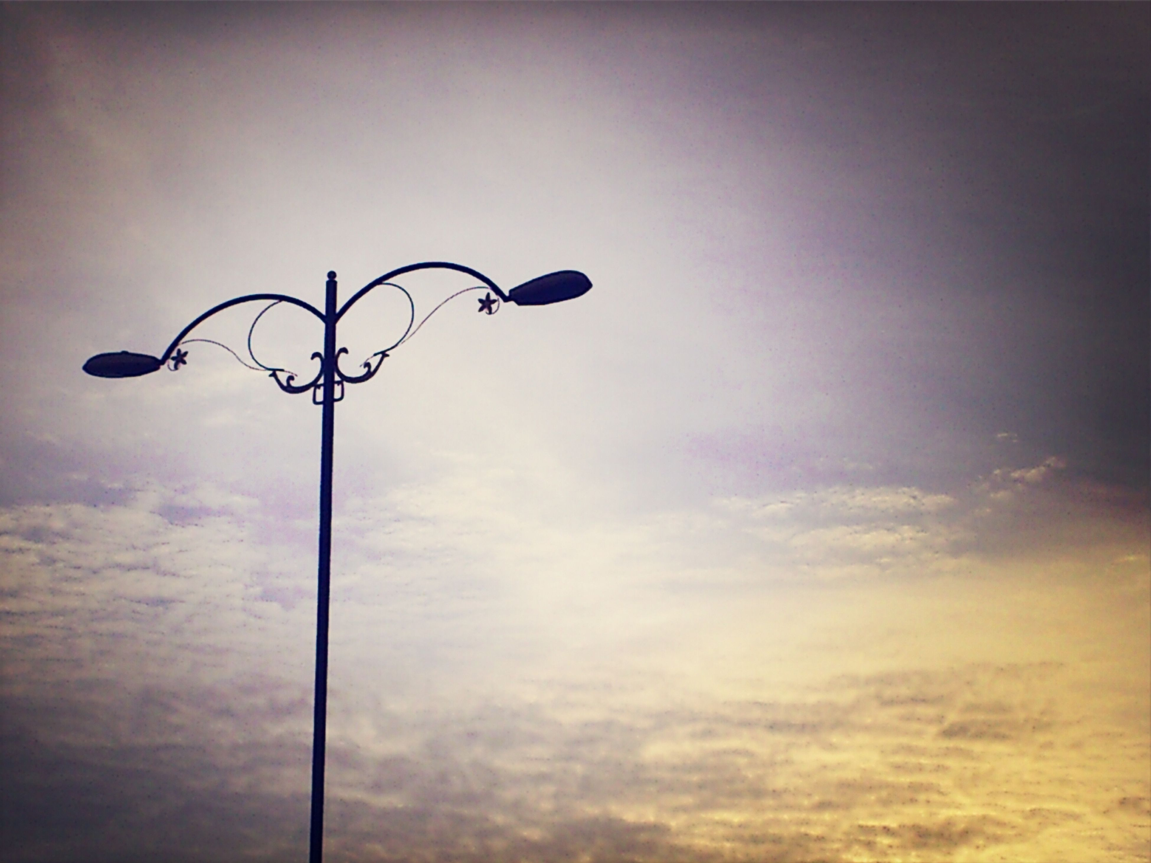 street light, low angle view, lighting equipment, sky, silhouette, pole, lamp post, cloud - sky, sunset, dusk, cloud, no people, electric light, electricity, outdoors, cloudy, copy space, nature, day, built structure