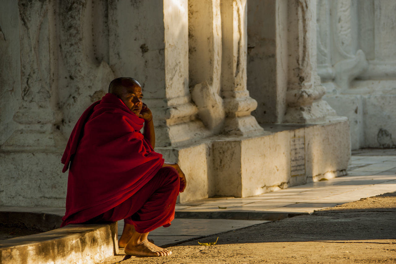 religion, spirituality, real people, red, traditional clothing, place of worship, one person, full length, ancient, architectural column, architecture, built structure, day, outdoors, people
