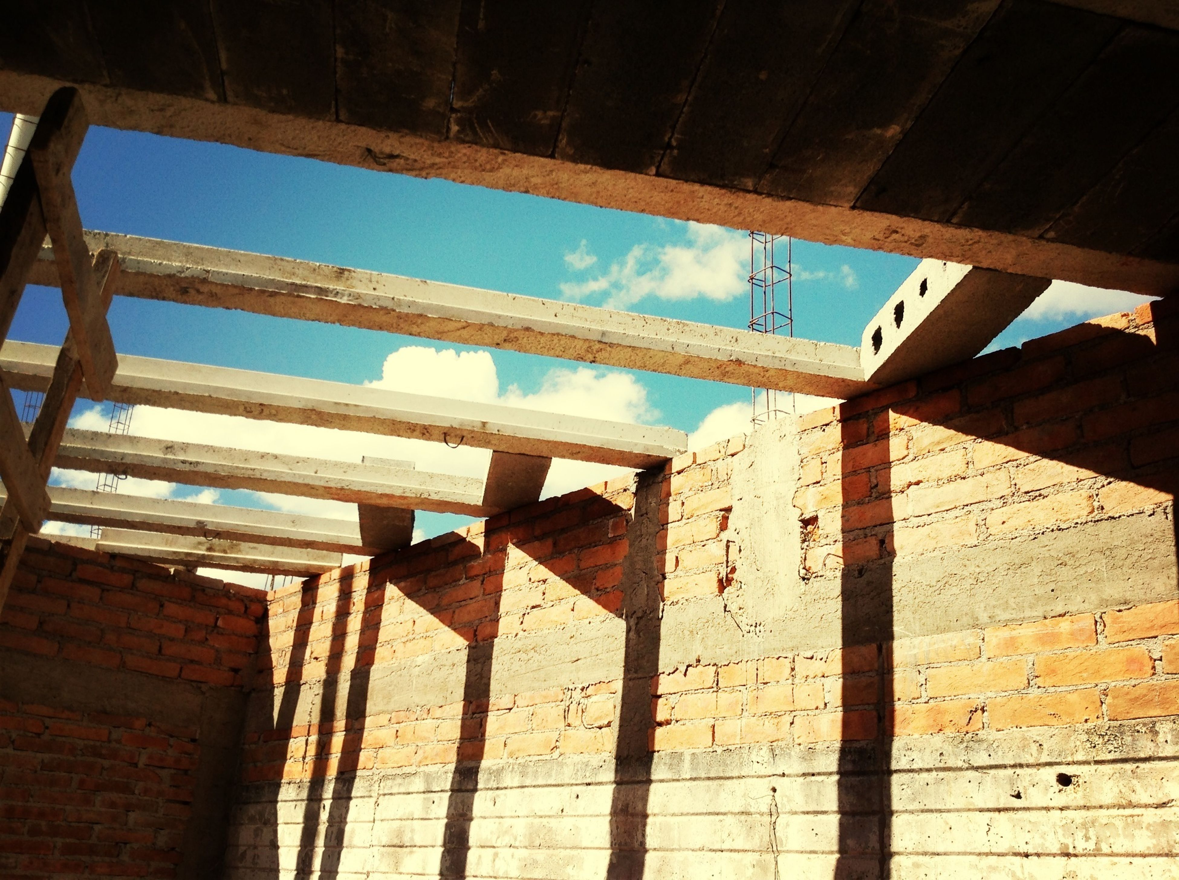 built structure, architecture, low angle view, building exterior, sunlight, sky, shadow, day, indoors, no people, wood - material, wall - building feature, railing, damaged, abandoned, old, building, metal, window
