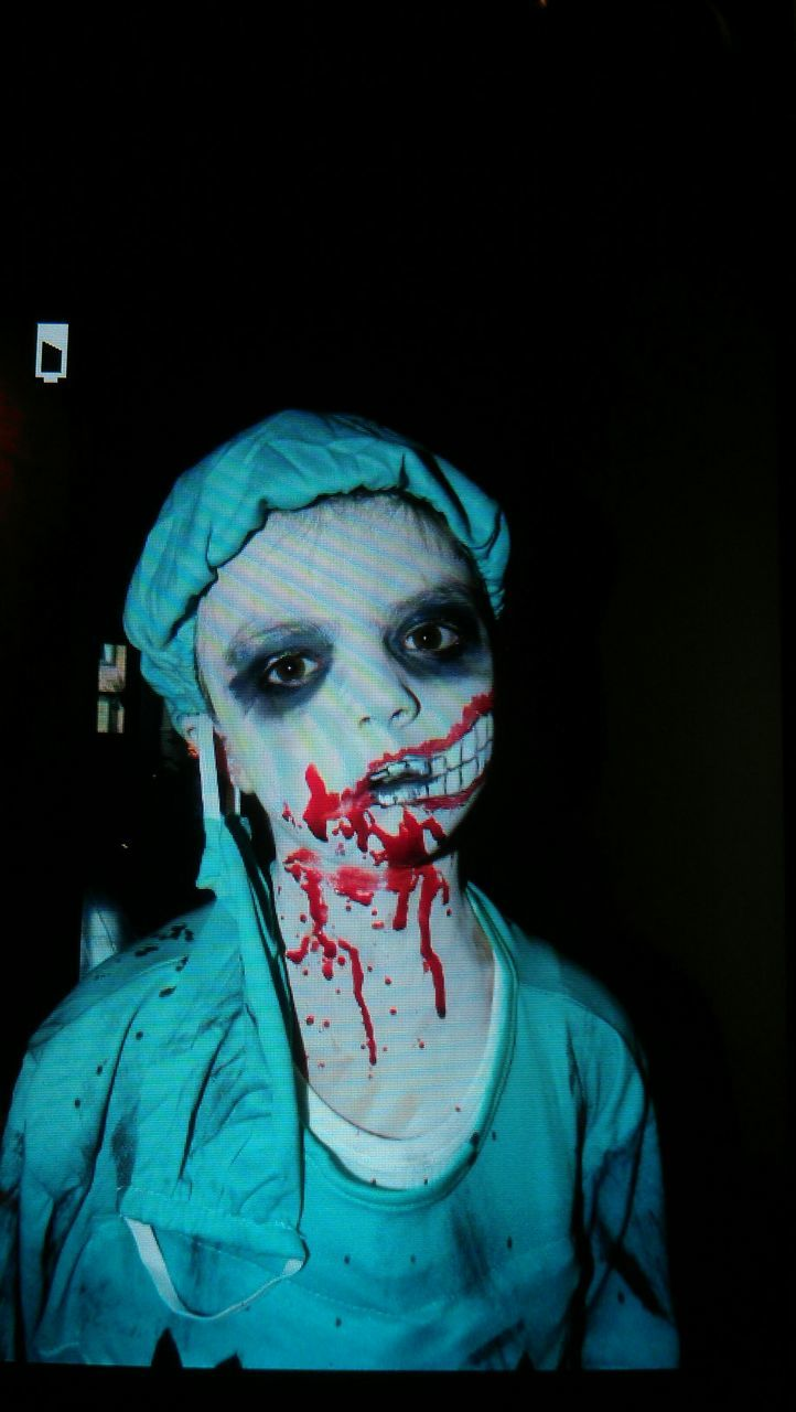 face paint, spooky, portrait, looking at camera, halloween, horror, one person, night, make-up, blue, real people, clown, black background, young adult, close-up, indoors, people