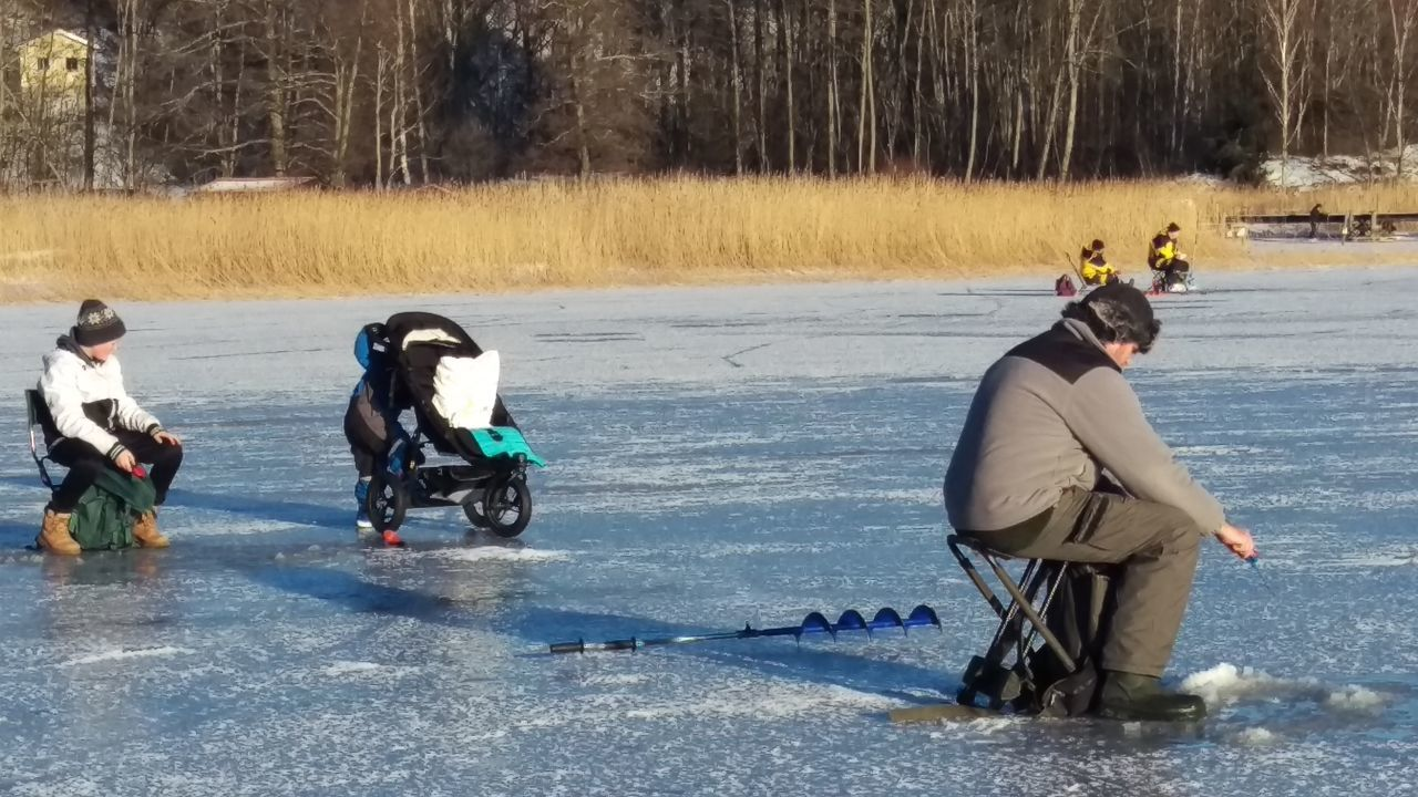 Family fishing day on a frozen lake Fishing Fishing Time Lake Frost Ice Frozen Family People Sweden Scandia Scandinavia January Winter Day Winter Cold Northern Europe Kolmården Östergötland