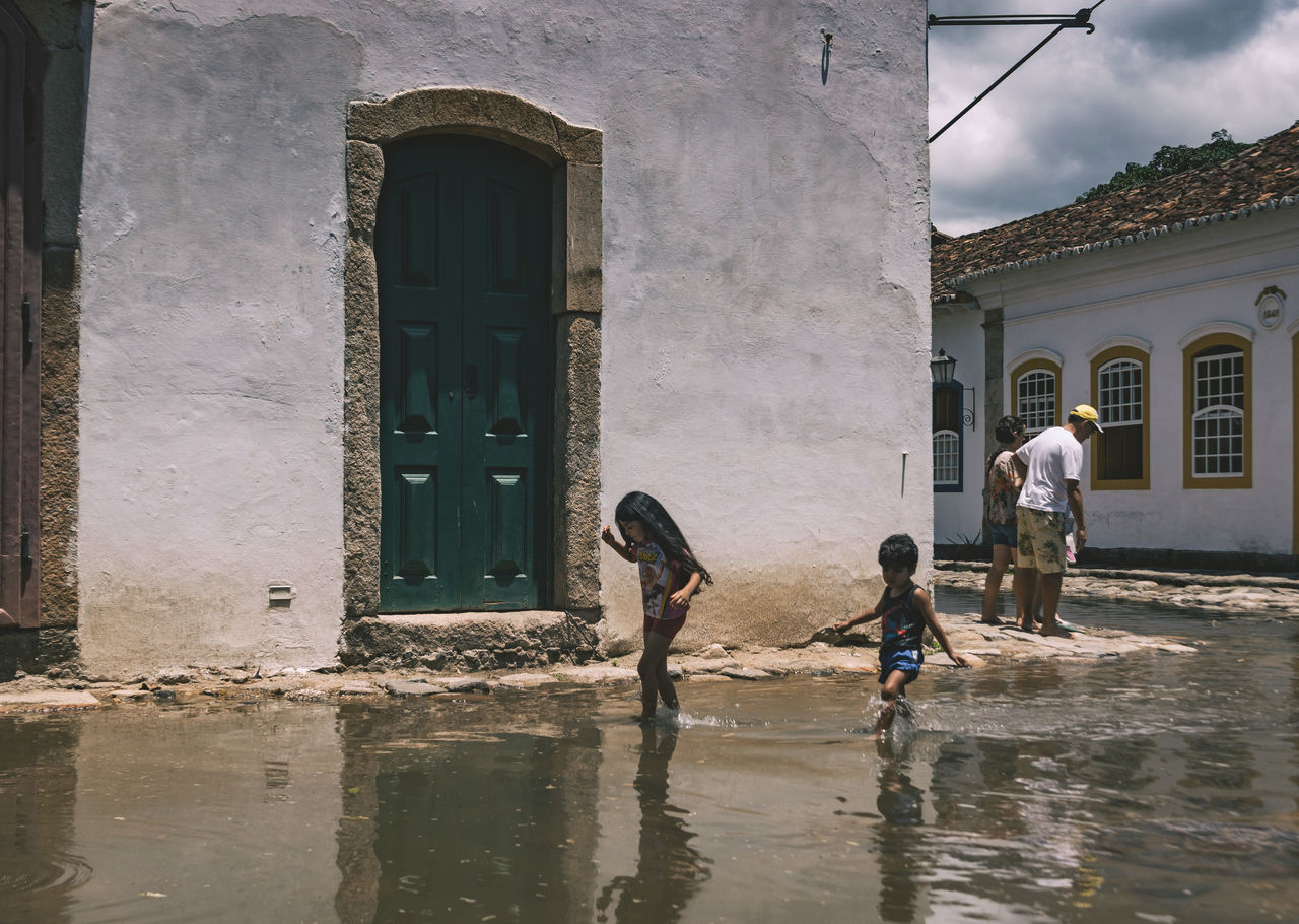 Two children making their way through the flooded streets of Parati. The others don't seem like they wanna get their feet dirty. Architecture Boy Boys Building Exterior Built Structure Childhood Day Flood Flooding Girl Girls Leisure Activity Lifestyles Men Outdoors Real People Standing Street The Street Photographer - 2017 EyeEm Awards Together Togetherness Walking Walking Around Water Women