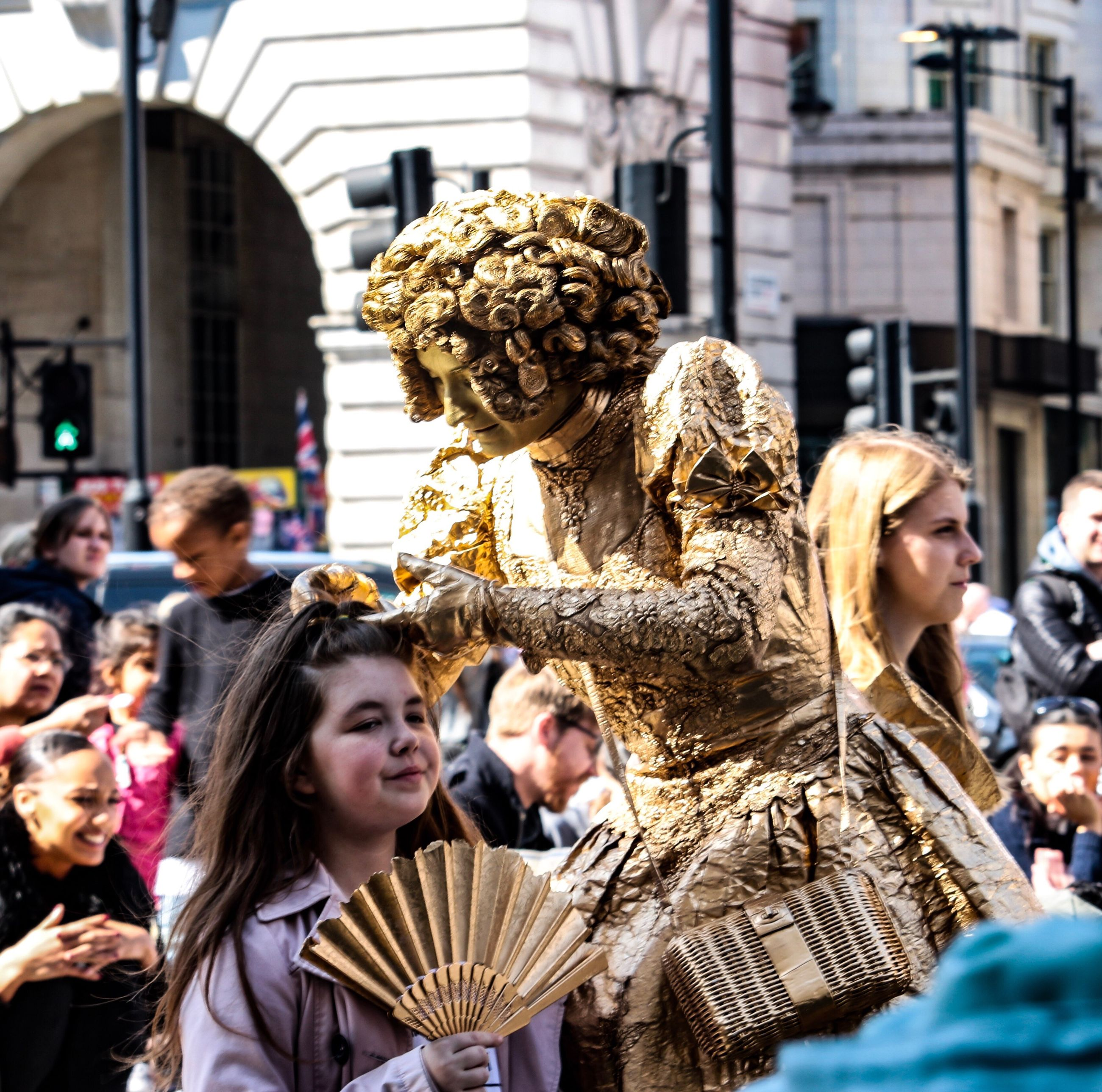 architecture, city, built structure, building exterior, statue, real people, leisure activity, medium group of people, men, outdoors, sculpture, musician, people, day, period costume, adult, adults only