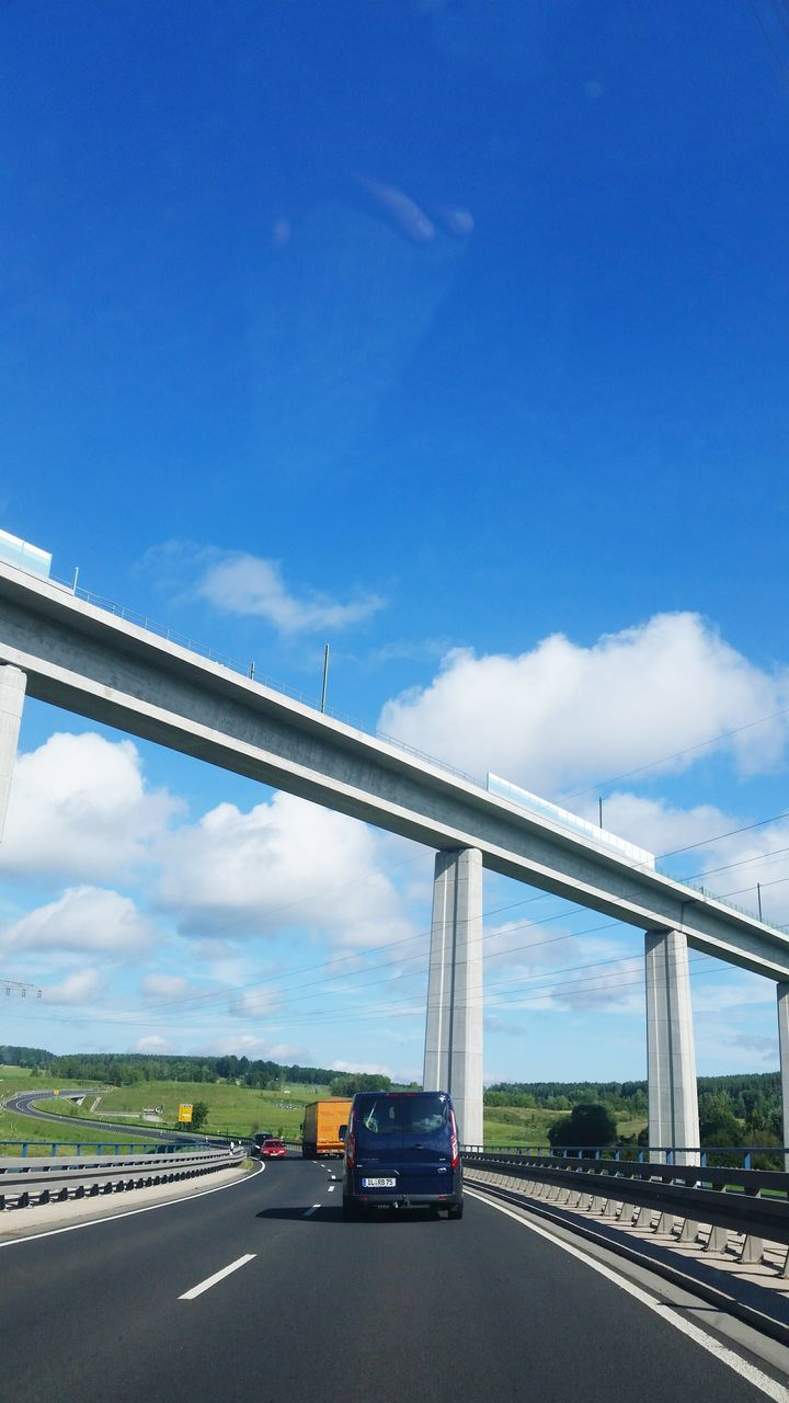 Low Angle View Of Bridge Over Car Moving On Road Against Cloudy Sky