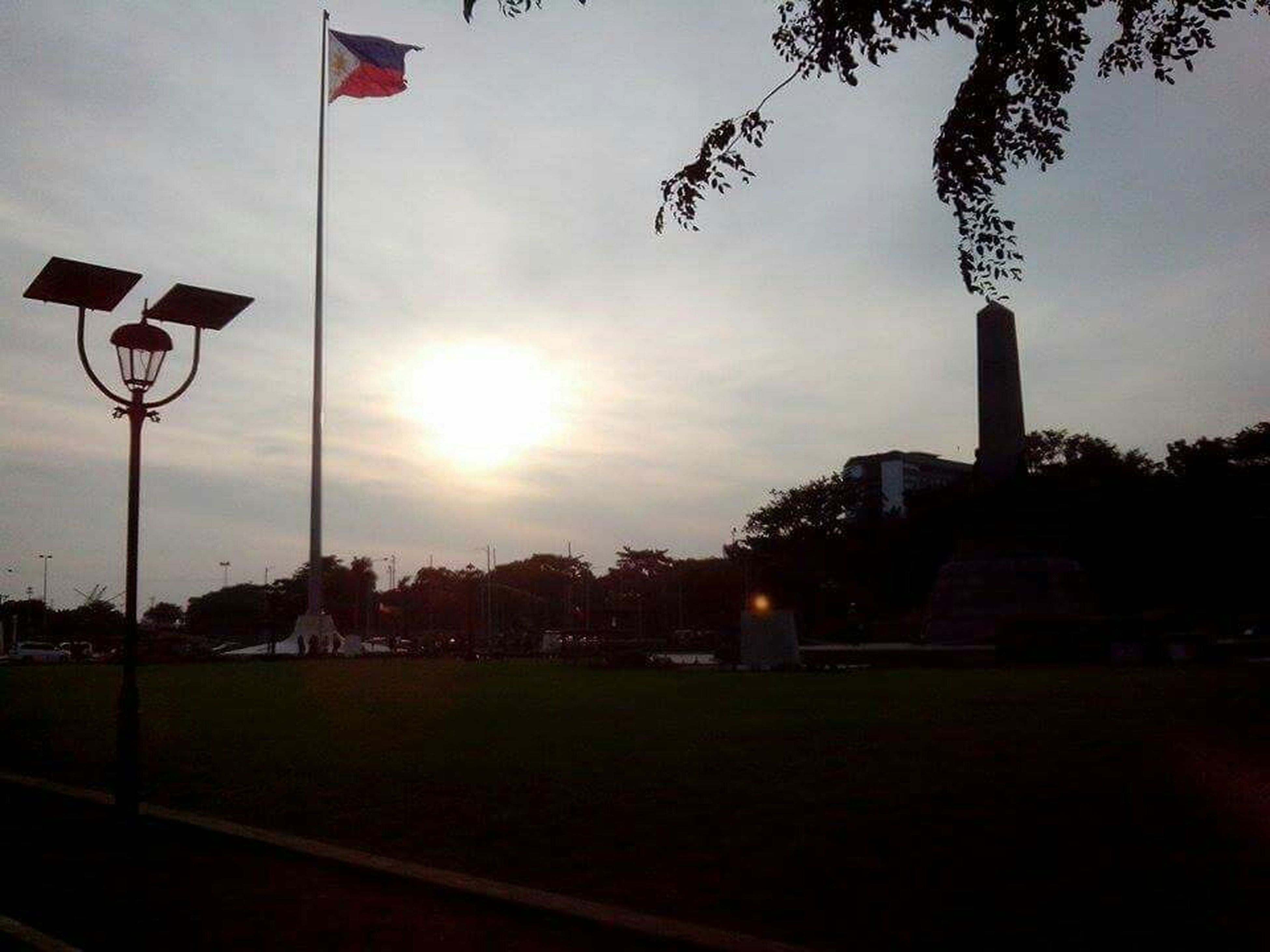 sun, tree, sky, street light, sunlight, sunbeam, sunset, lens flare, grass, built structure, building exterior, architecture, cloud - sky, park - man made space, flag, nature, outdoors, silhouette, pole, no people