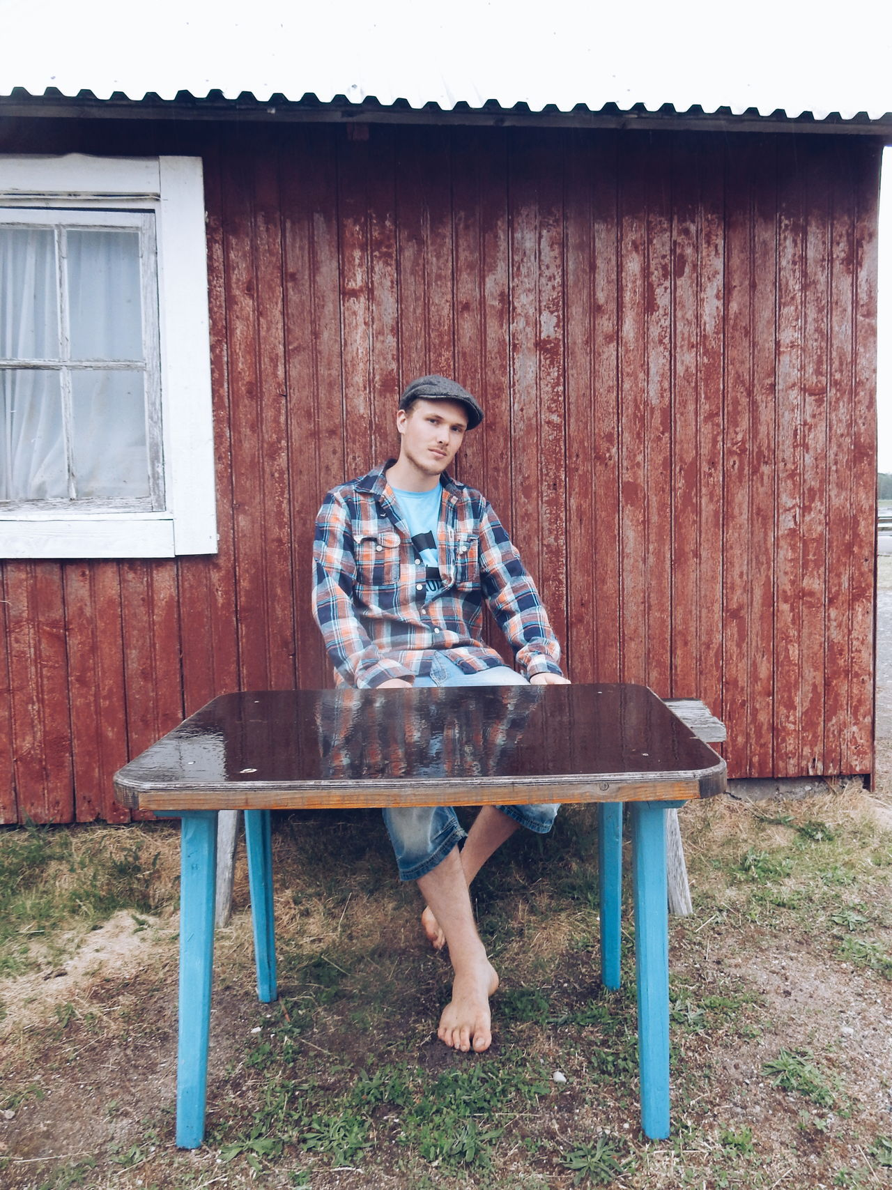 young man sitting on a bench outside a fishing cottage Young Adult Young Man Outdoors Cottage Cottage Life House Fishermenvillage Fisherman Sitting Uniqueness TCPM Live For The Story The Portraitist - 2017 EyeEm Awards