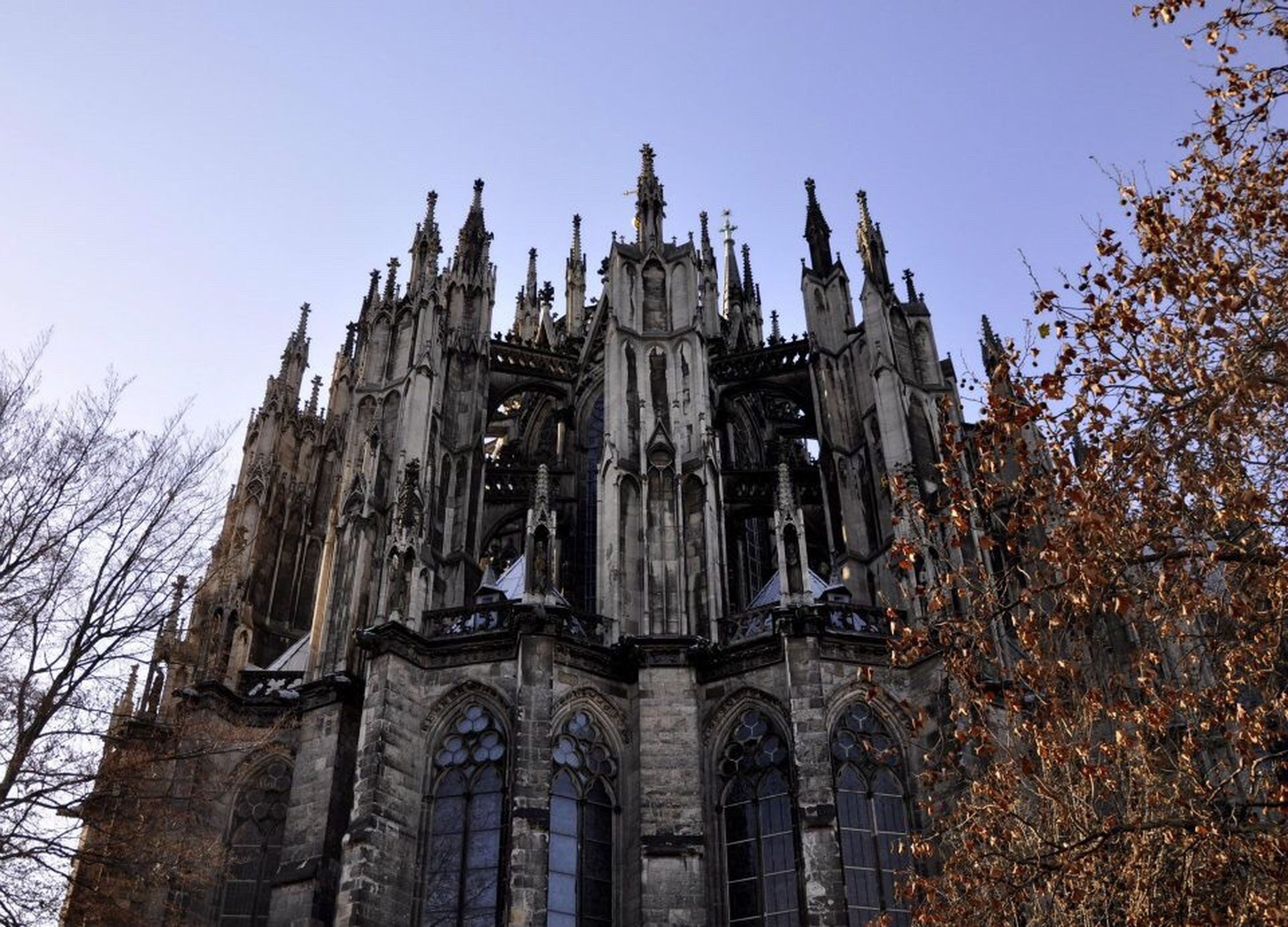 religion, church, spirituality, architecture, place of worship, built structure, building exterior, low angle view, cathedral, sculpture, clear sky, spire, architectural feature, steeple, outdoors, history, milan cathedral, gothic style, sky, arch, high section, facade, culture, famous place, day, notre dame de paris, duomo di milano, gothic