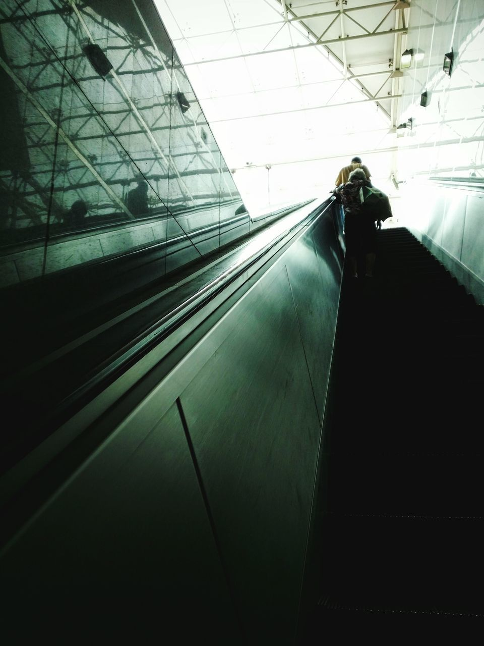 Low Angle View Of People On Escalator In Building