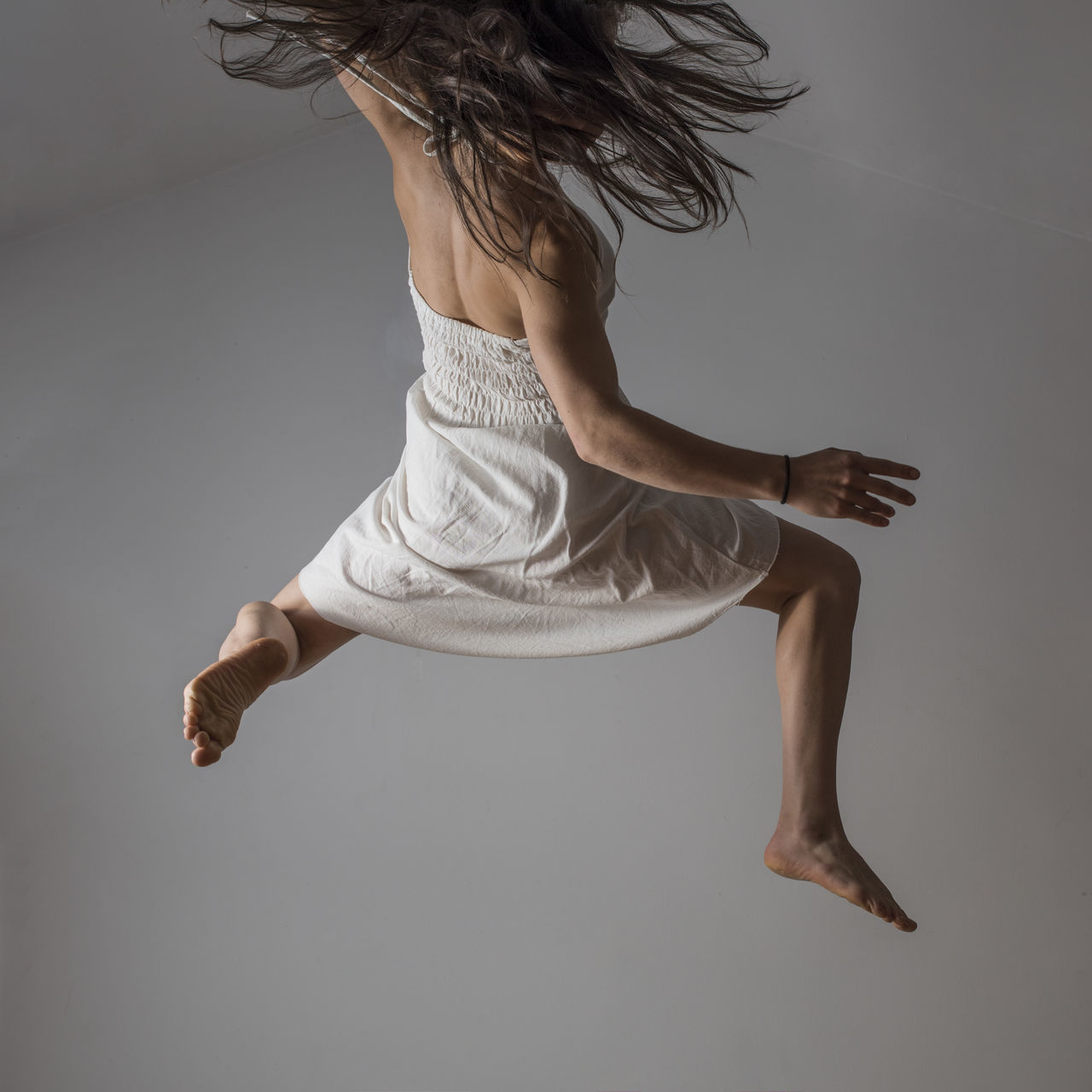 Jumping dancer captured in the air. Studio photography. Ballet Ballet Dancer Barefoot Contemporary Contemporary Art Contemporary Dance Dancer Female Indoors  Jumping Long Hair Loose Hair Low Angle View Mid-air Motion Motion Freeze Movement One Light Source One Person People Real People Studio Shot White Background White Dress Young Adult