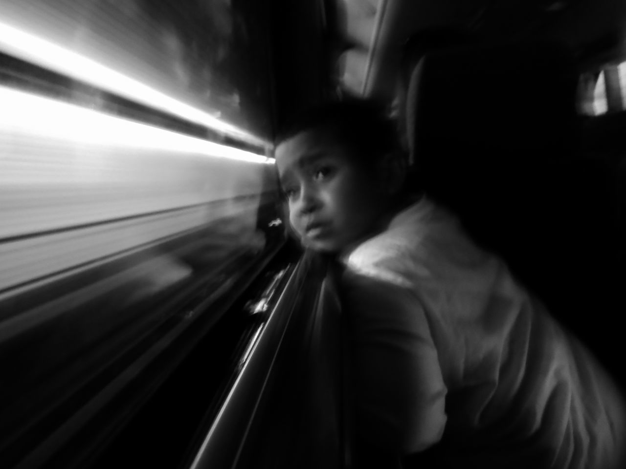 Curious Boy Looking At Light Trail Through Glass Window While Traveling In Bus