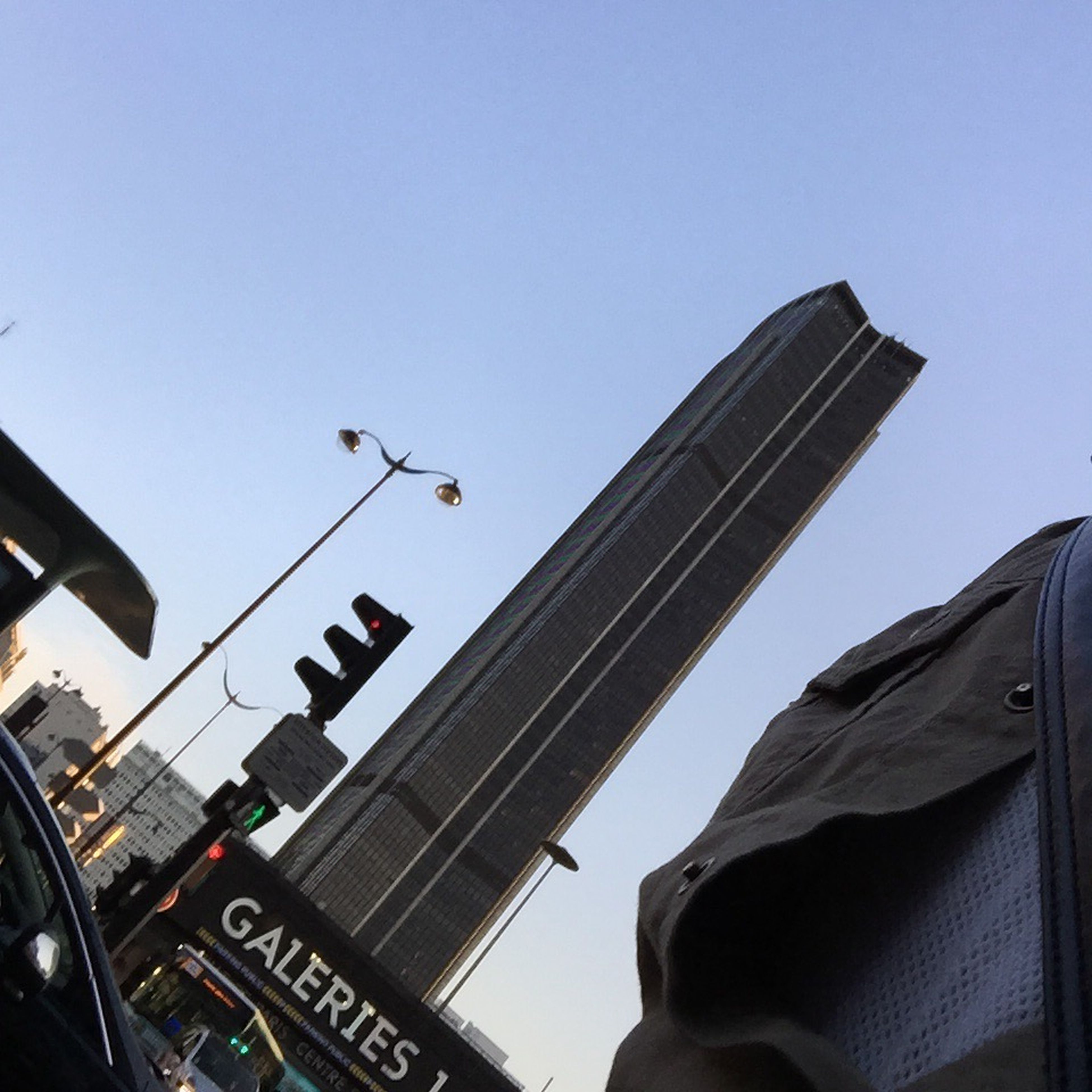 low angle view, clear sky, architecture, building exterior, built structure, transportation, city, communication, car, text, mode of transport, copy space, western script, land vehicle, blue, day, tower, skyscraper, tall - high, travel