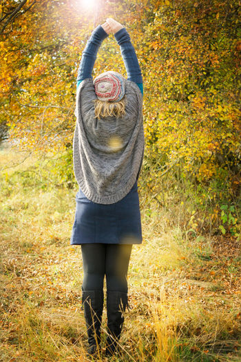 Woman stretches the back in autumn scenery Backside Cardigan Fashion Woman Arms Up Atmospheric Autumn Autumn Scenery Back Gymnastics Back Pains Blond Hair Deciduous Forest Full Length High Boots Leaf Lens Flares Lifestyles Nature Outdoors Poncho Skirt Standing Stretch Stretches Herself Warm Colours