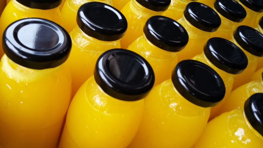Arrangement Backgrounds Bottles Close-up Collection Fresh Orange Juice Freshness Full Frame High Angle View In A Row Indoors  Juice In Bottles Large Group Of Objects Medium Group Of Objects No People Order Repetition Still Life Vibrant Color Yellow