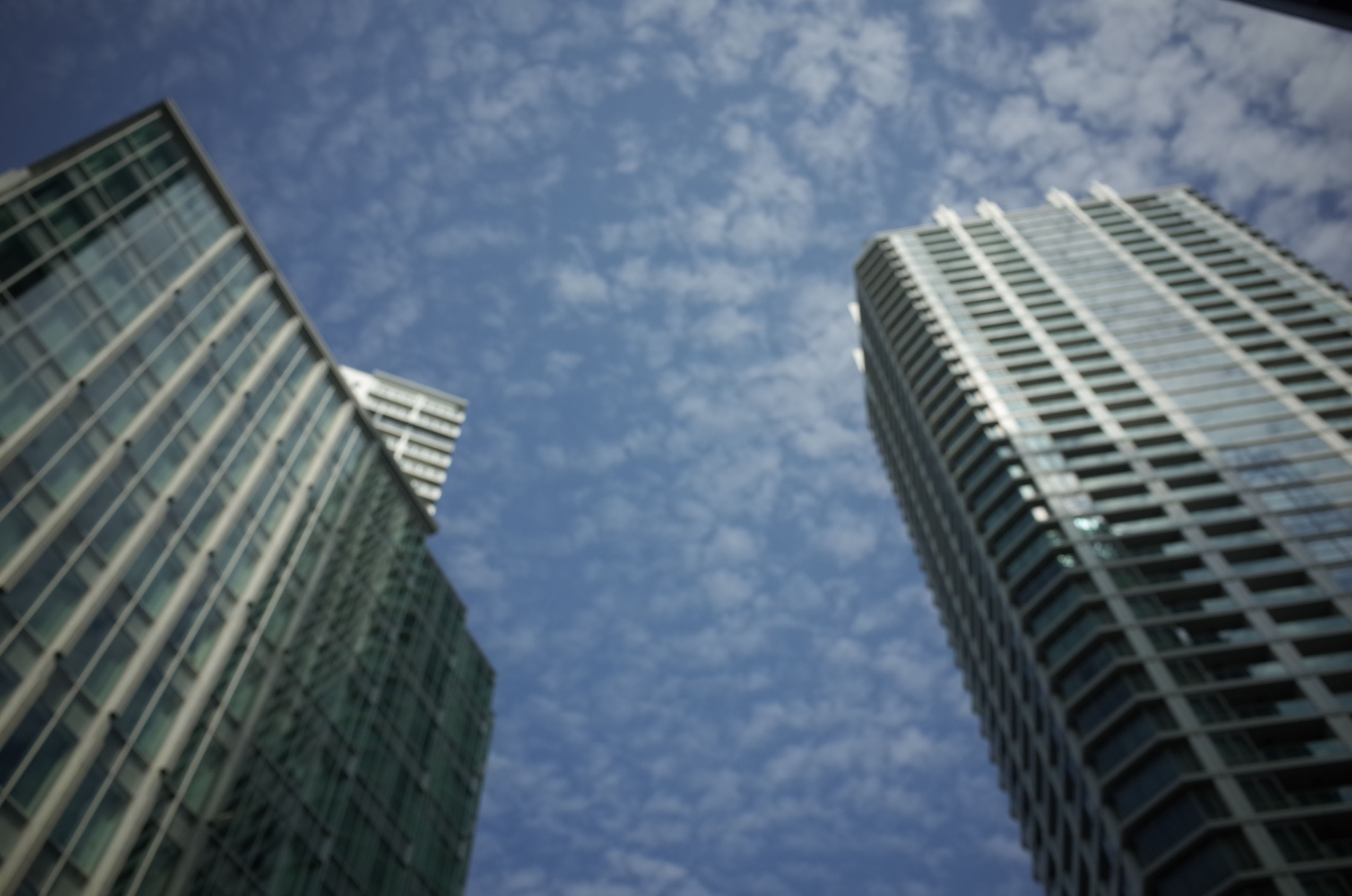 building exterior, architecture, low angle view, built structure, modern, sky, skyscraper, office building, city, tall - high, cloud - sky, tower, building, reflection, glass - material, cloud, cloudy, directly below, tall, day