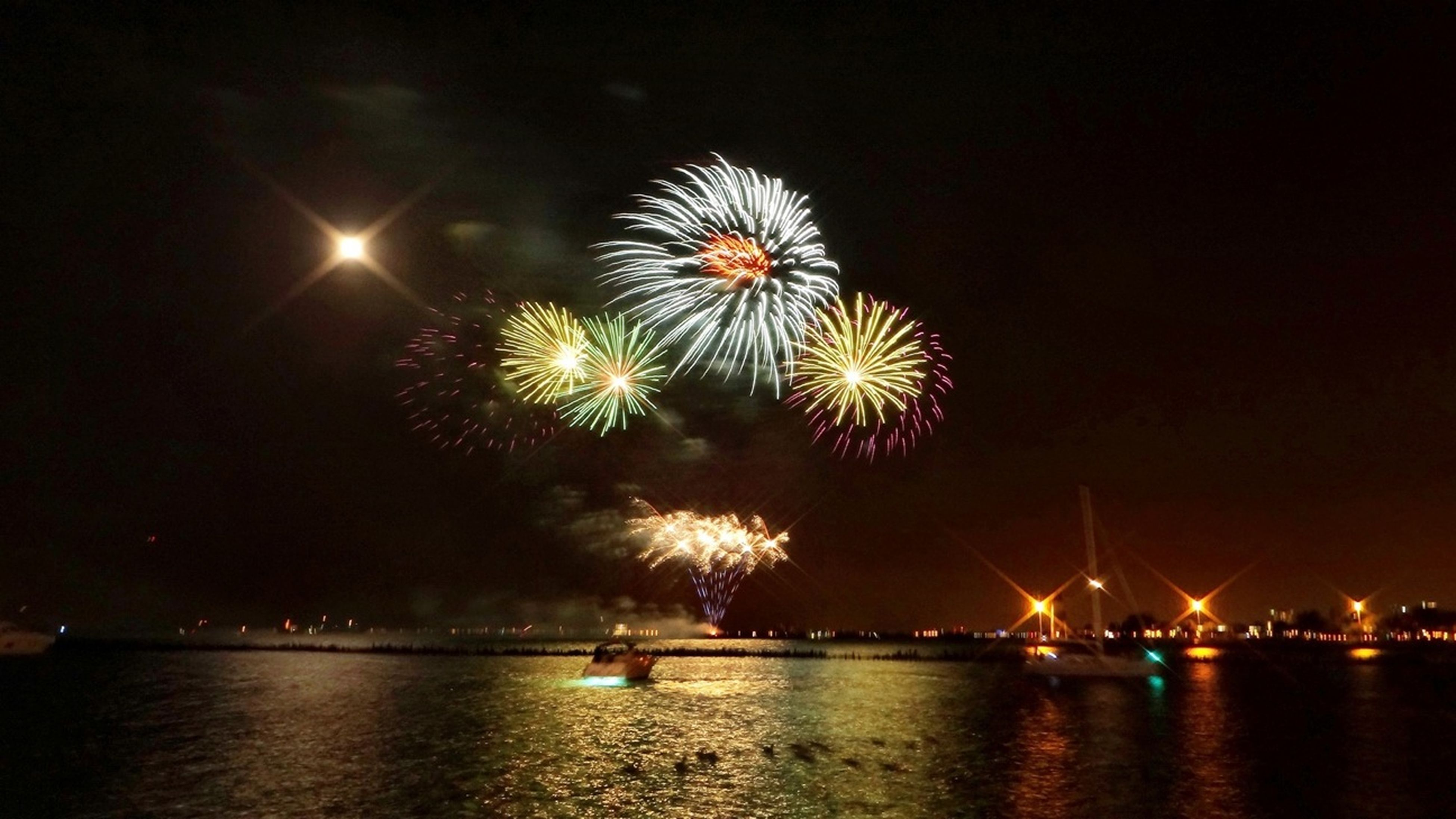 night, illuminated, water, firework display, waterfront, exploding, arts culture and entertainment, celebration, long exposure, firework - man made object, sparks, glowing, sea, sky, reflection, river, motion, firework, event, entertainment