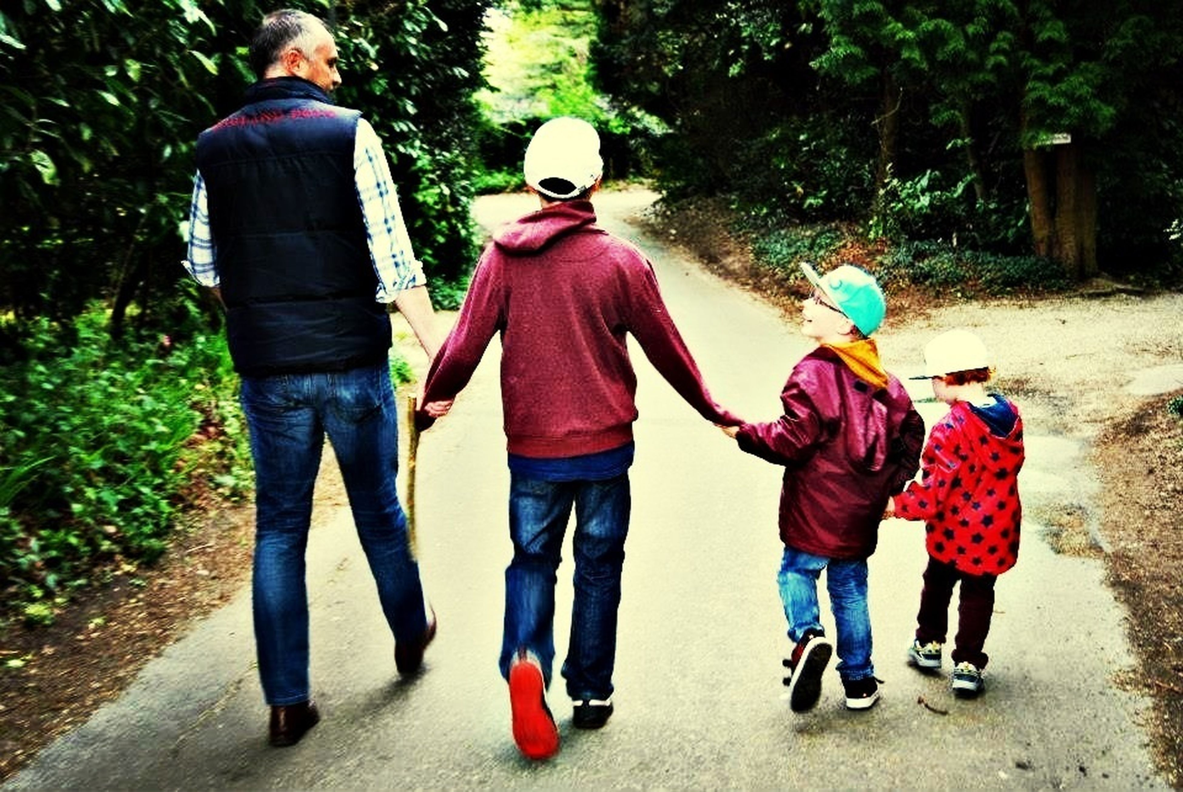 full length, togetherness, lifestyles, casual clothing, rear view, bonding, leisure activity, childhood, men, boys, love, walking, family, girls, street, family with one child, holding hands, friendship