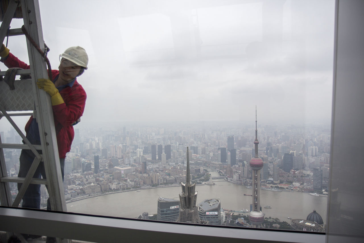 building exterior, built structure, fog, one person, architecture, day, window, cityscape, city, real people, occupation, working, outdoors, skyscraper, standing, men, industry, protective workwear, manual worker, window washer, sky, nature, people