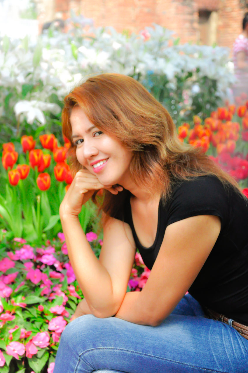 Portrait Of Beautiful Woman Sitting By Plants