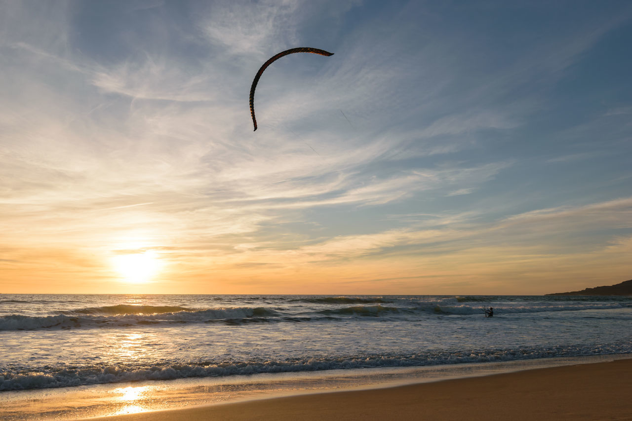 A Kitesurfer going into the Atlantic Ocean at a colorful sunset with his Kite high up in the air in Tarifa, Spain. Action Sports Athletic Beach Beauty In Nature Board Day Extreme Sports Hobby Horizon Over Water Kite Kitesurf Kitesurfing Ocean Scenics Sea Summer Sunset Surf Surfer Tranquility Water Watersport