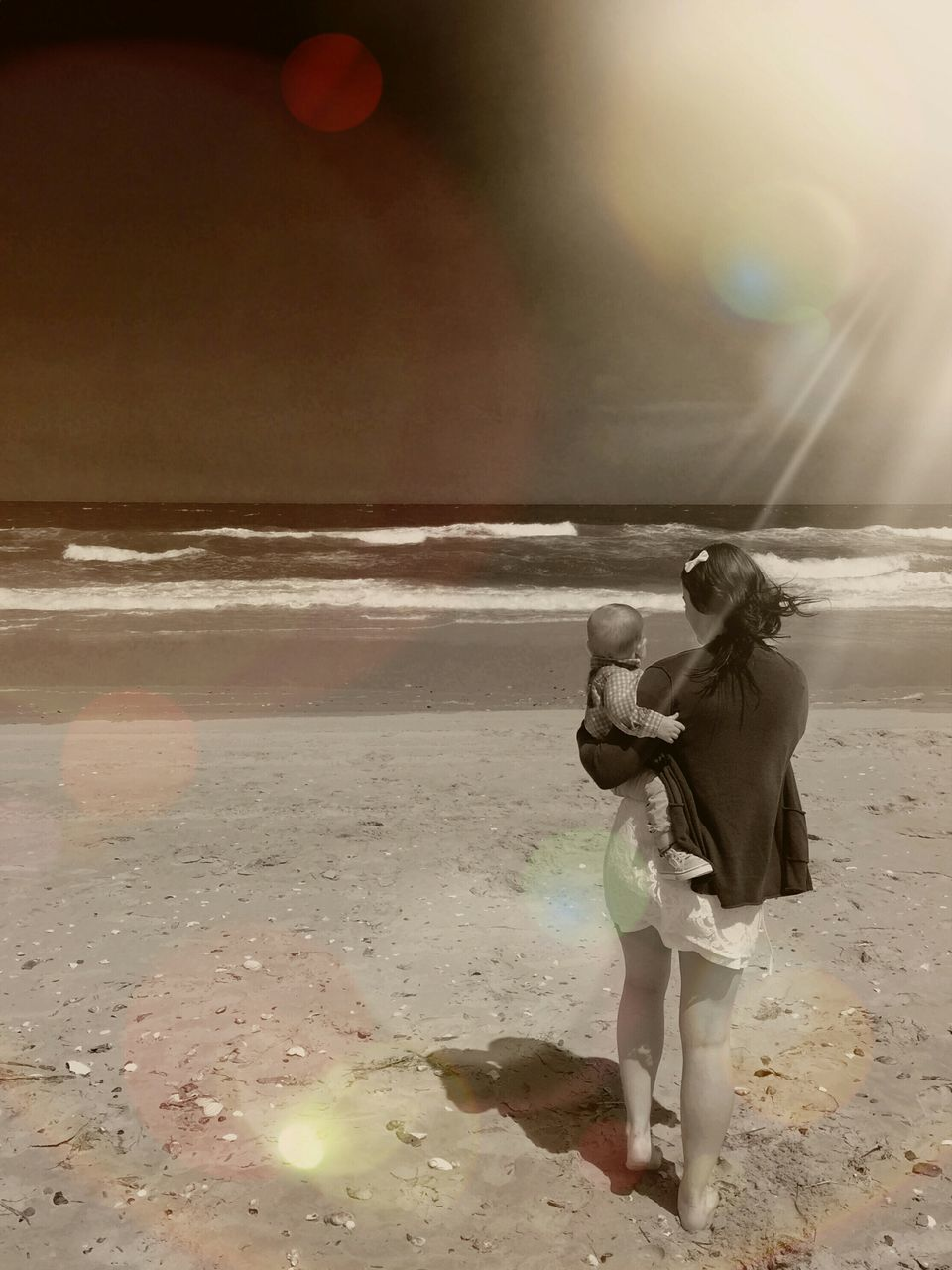 Rear View Of Mother Carrying Son At Beach Against Sky