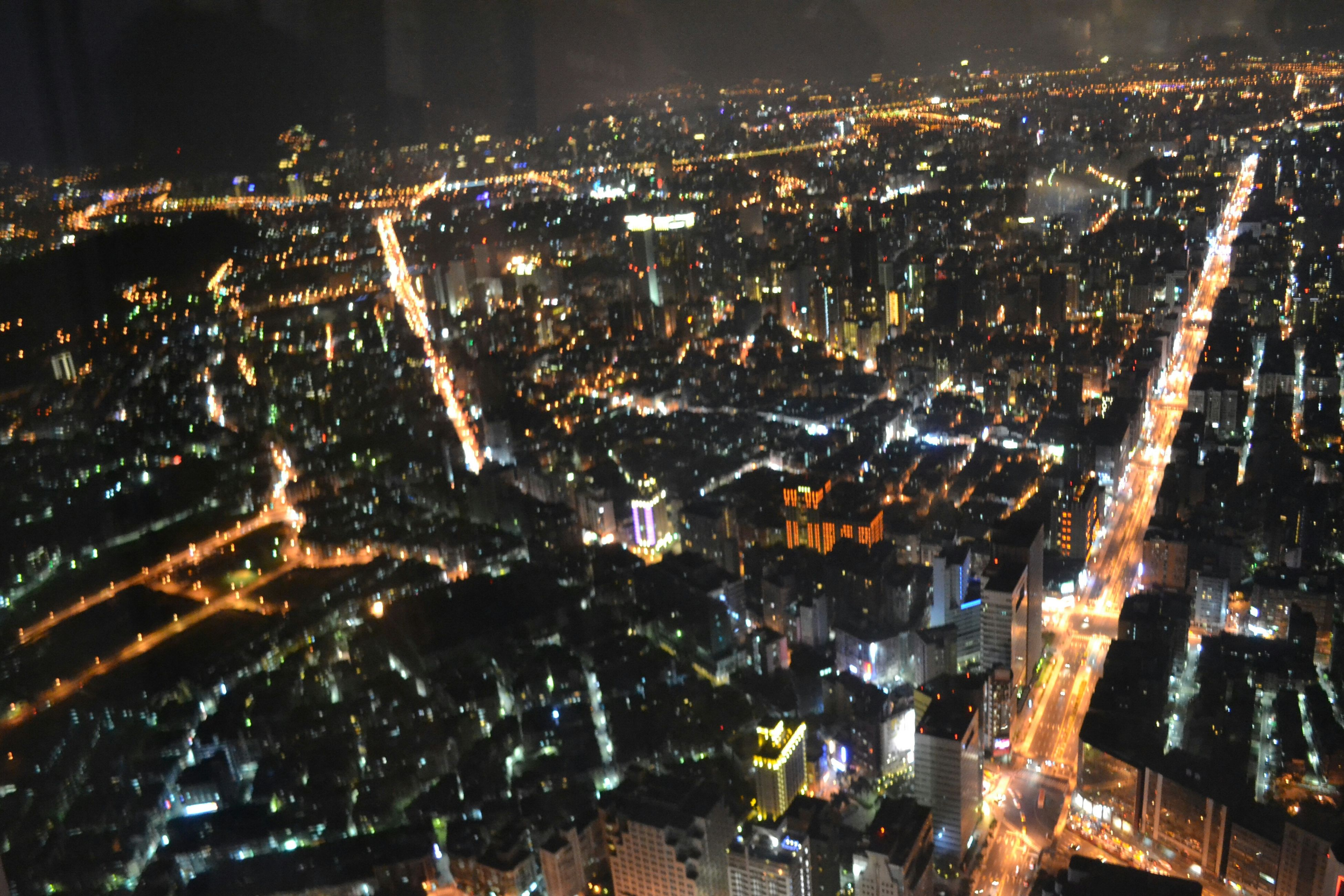 cityscape, night, illuminated, city, crowded, building exterior, architecture, aerial view, built structure, high angle view, residential district, residential building, city life, skyscraper, residential structure, capital cities, community, travel destinations, outdoors, tower