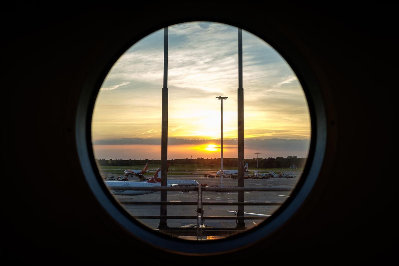 Airport Atmospheric Mood Bullseye Circle Cloud Cloud - Sky Cloudscape Hamburg Majestic Mode Of Transport Nature No People Orange Color Personal Perspective Sea Sky Sun Sunset Transportation Window