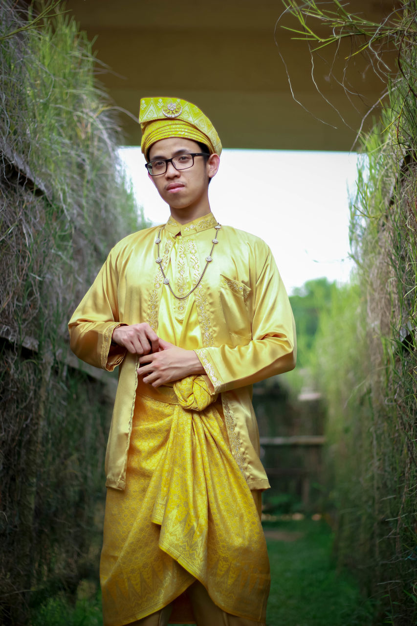 front view, standing, one person, yellow, cultures, traditional clothing, real people, day, young adult, outdoors, people