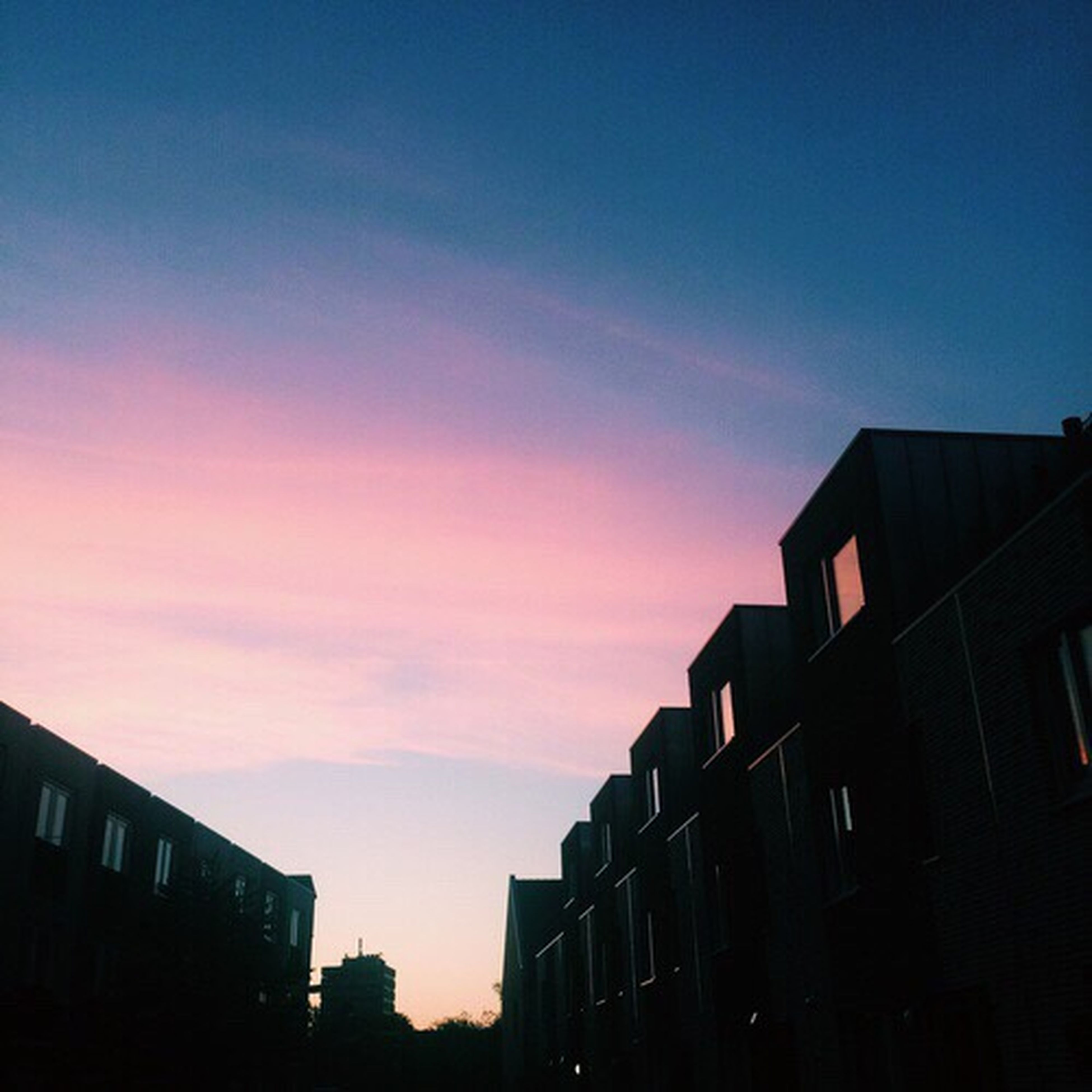 building exterior, architecture, built structure, sunset, residential structure, residential building, low angle view, sky, city, building, blue, residential district, outdoors, orange color, no people, cloud, cloud - sky, city life, high section, nature, beauty in nature