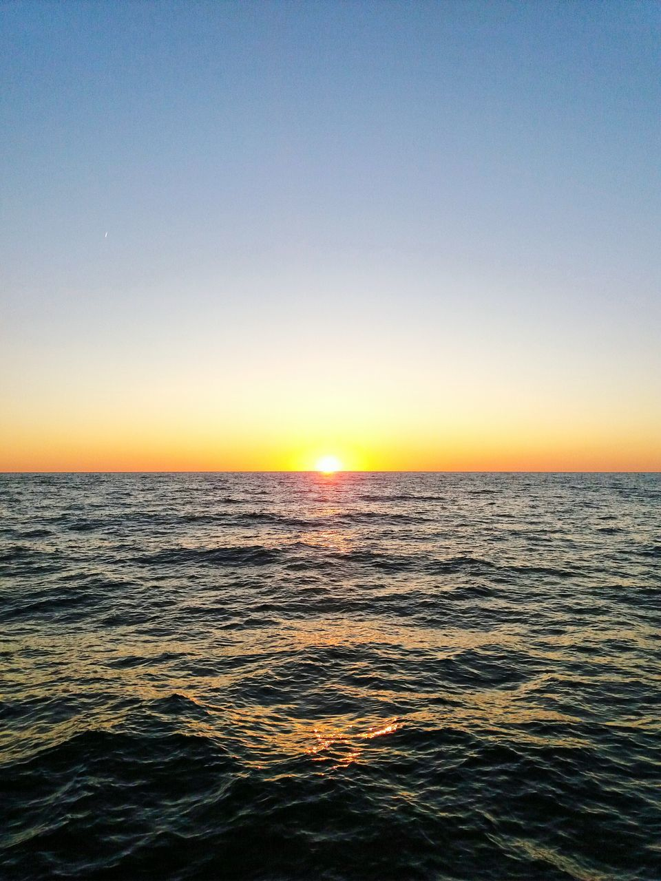 sea, sunset, scenics, beauty in nature, water, nature, tranquil scene, horizon over water, tranquility, rippled, idyllic, clear sky, outdoors, waterfront, no people, sun, sky, sunlight, wave, day