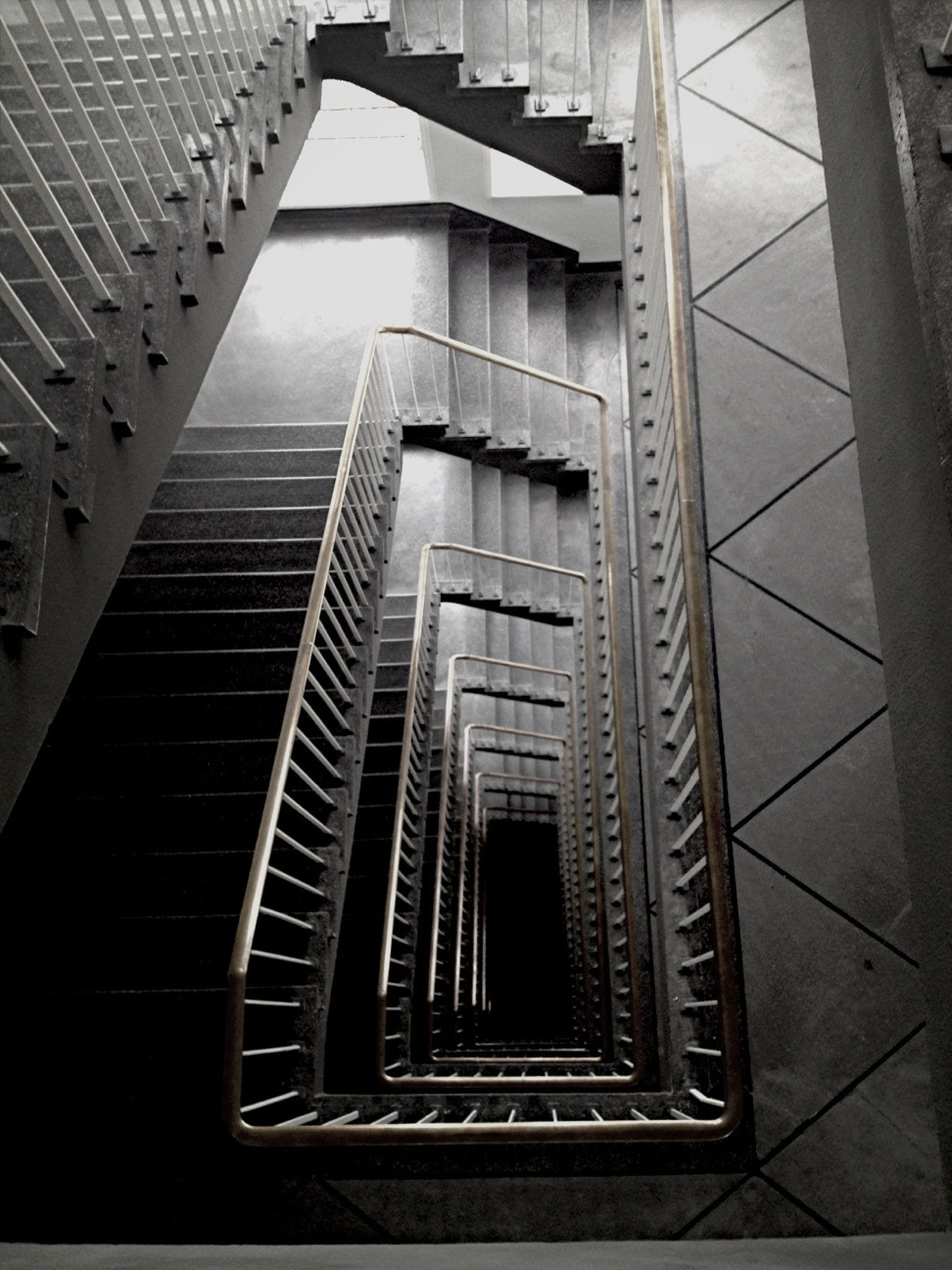 architecture, staircase, steps and staircases, steps, built structure, railing, indoors, low angle view, building exterior, building, pattern, stairs, directly below, spiral staircase, modern, high angle view, no people, diminishing perspective, spiral, the way forward