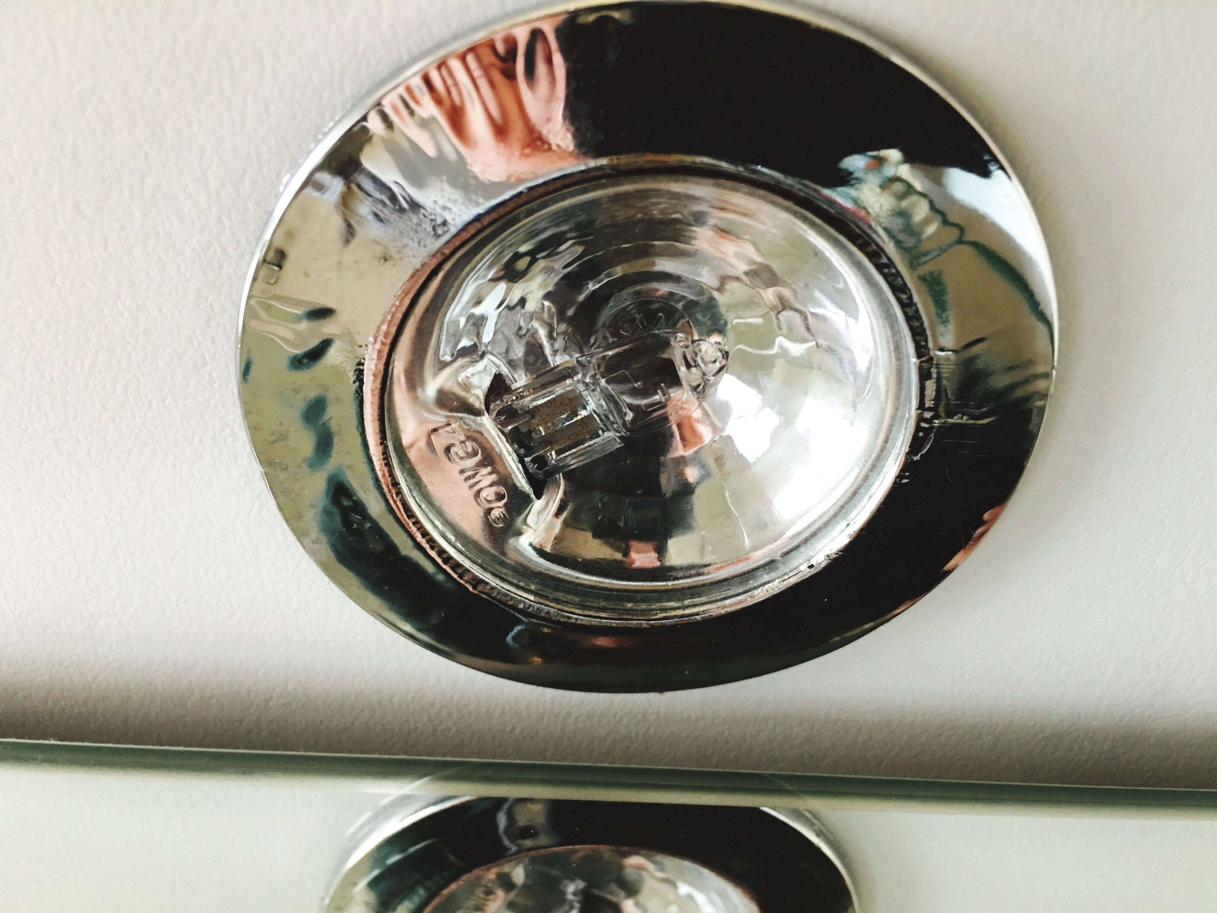 indoors, reflection, close-up, technology, glass - material, high angle view, circle, part of, mirror, photography themes, camera - photographic equipment, directly above, transparent, old-fashioned, metal, photographing, sink, person