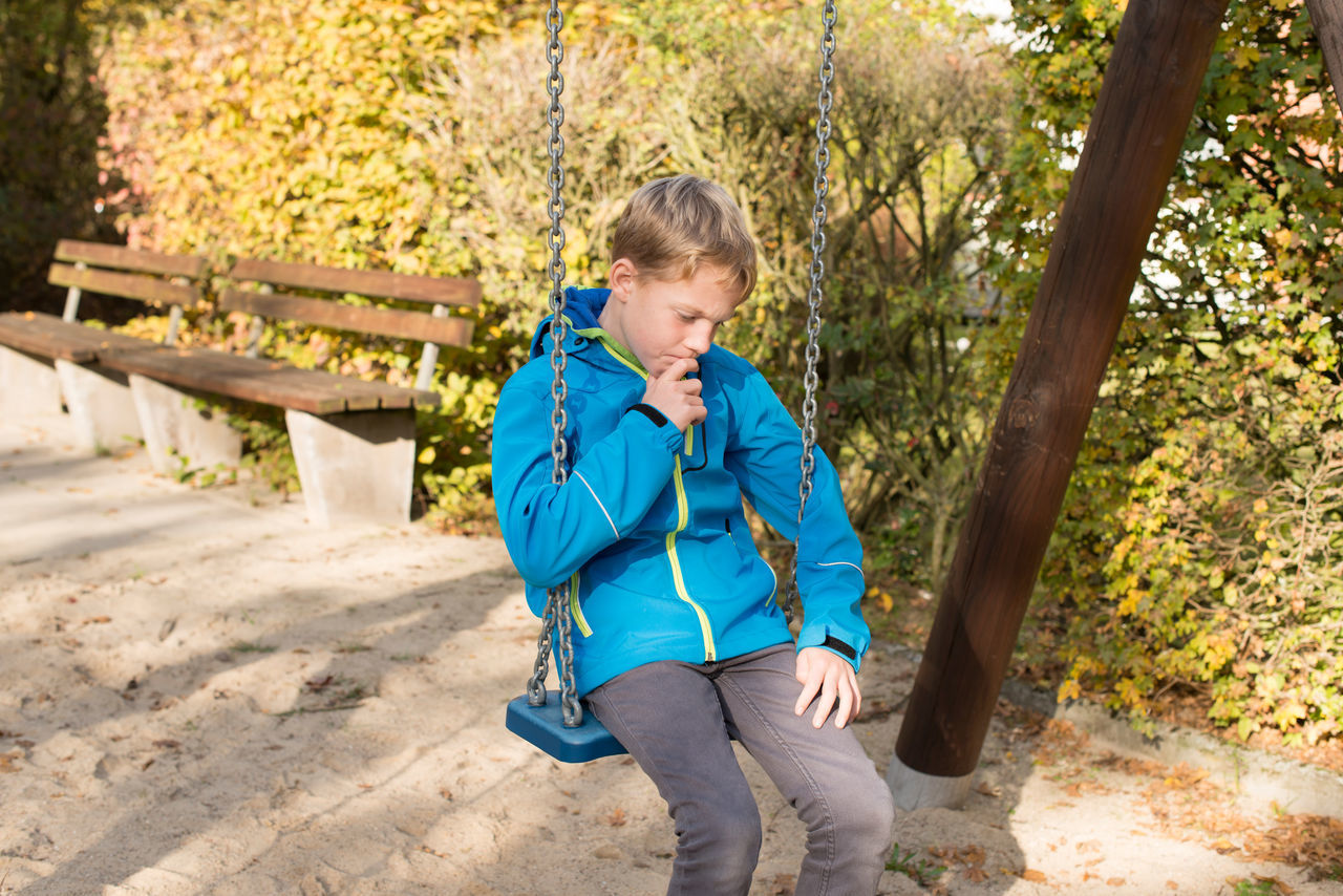 Child on swing Alone Boy Chain Child Childhood Depressed Depression Despair Fun Happy Leisure Lonely Moving Playground Playing Rocking Sad Shy Unhappy Young